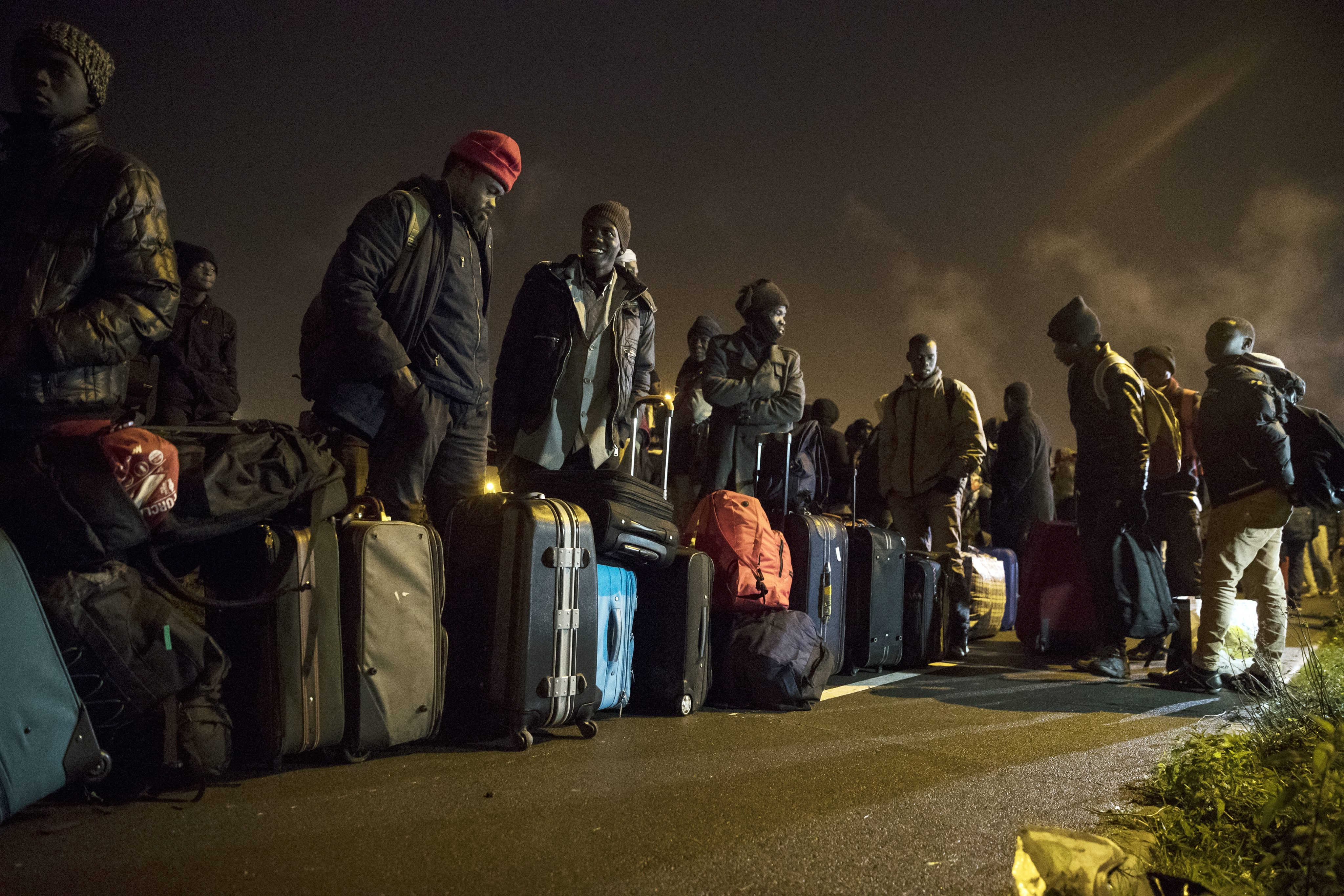 """Z Calais zostanie wywiezionych ponad 6,4 tys. osób. W poniedziałek pod halę służącą za dworzec podstawiono 60 autobusów. Ewakuacja ma trwać ponad tydzień, ale władze już na środę zapowiadają początek burzenia baraków i czyszczenia pozostałości po zwolnionych fragmentach """"dżungli"""". fot. EPA/ETIENNE LAURENT Dostawca: PAP/EPA."""