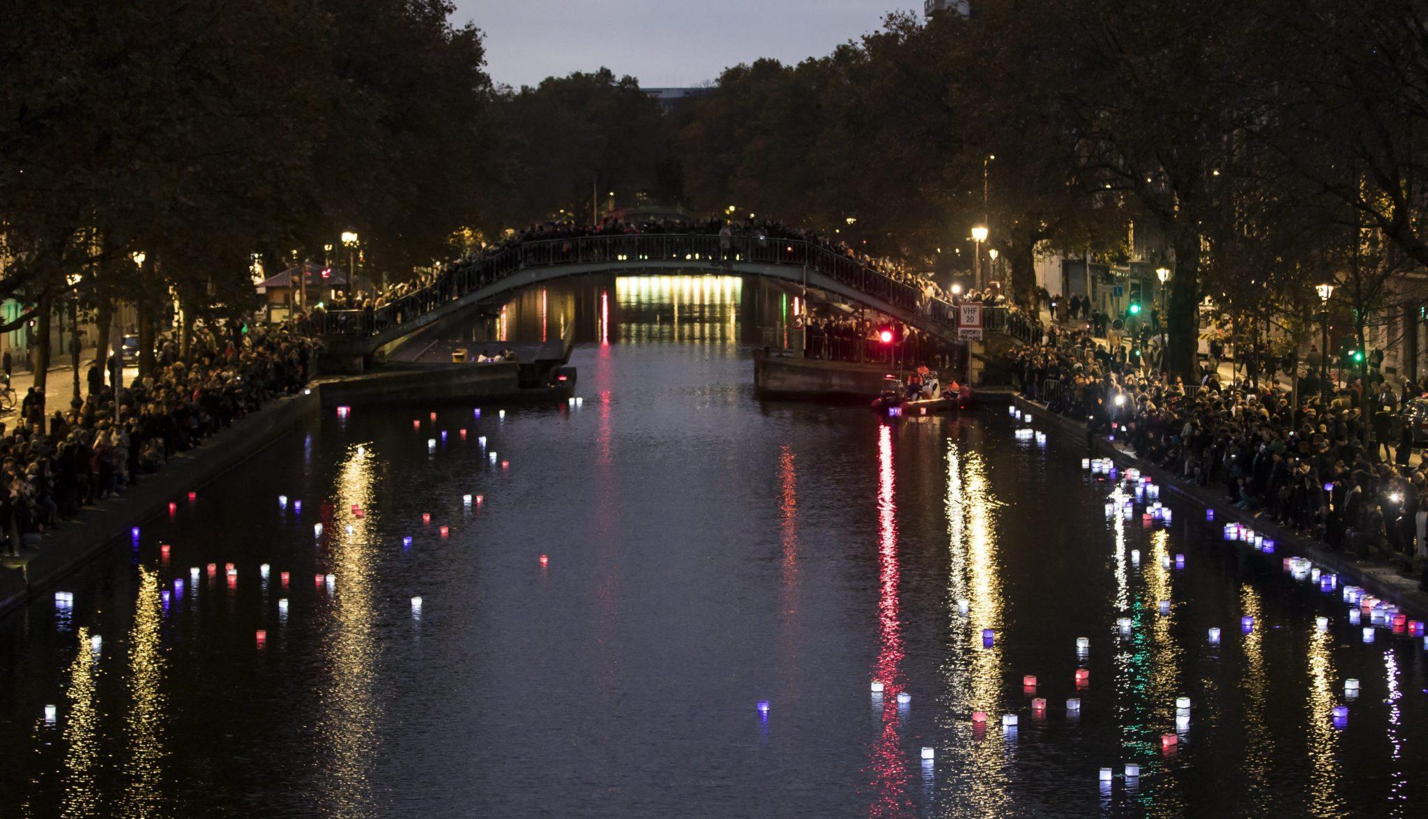 Ludzie puszczają kanałem Saint Martin lampiony w barwach narodowych Francji w celu upamiętnienia ofiar zeszłorocznego zamachu.