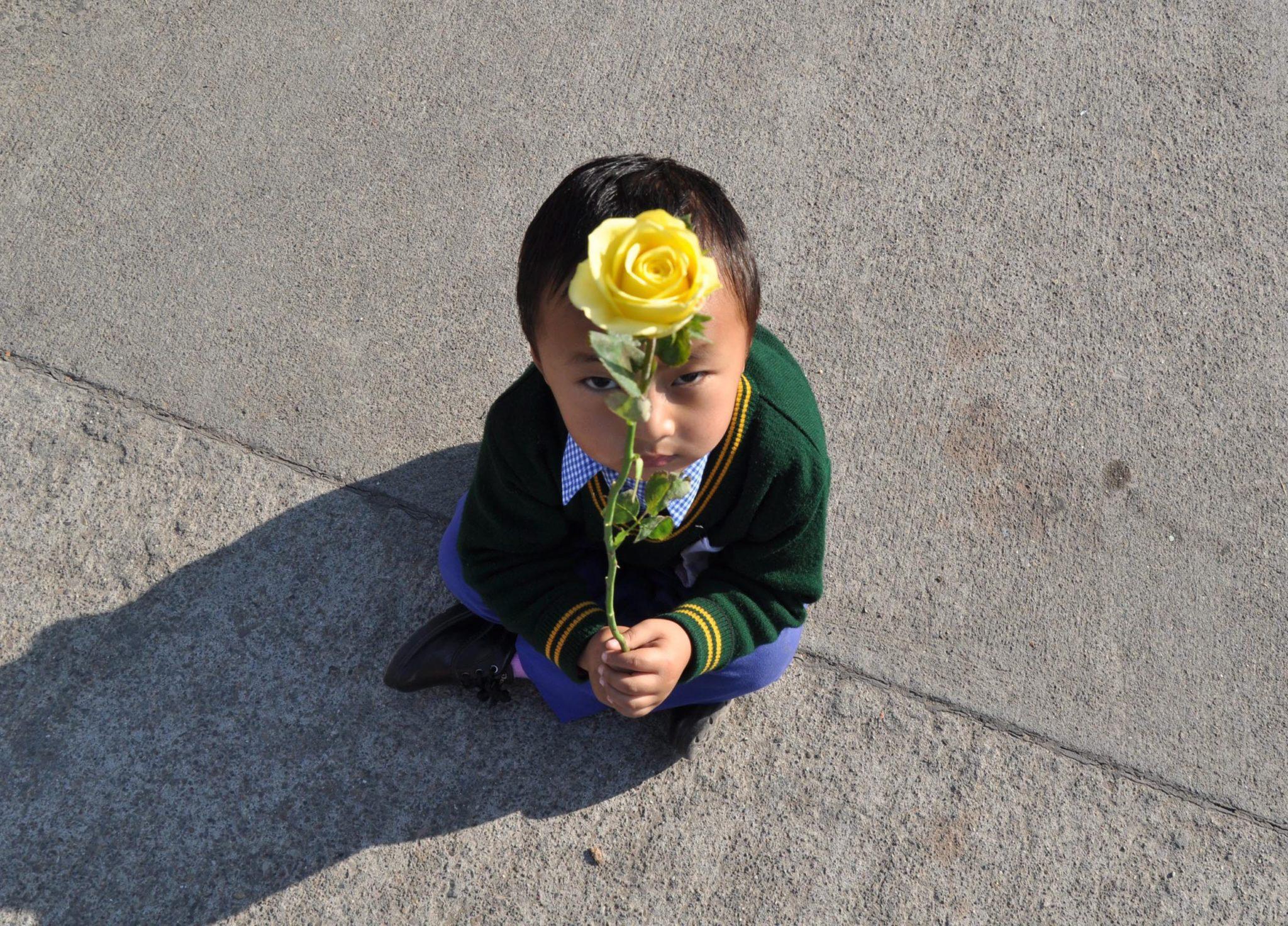 Tybet: mały chłopiec wita tybetańskiego przywódcę duchowego Dalajlamę, po jego powrocie z Japonii (foto. PAP/EPA/SANJAY BAID)