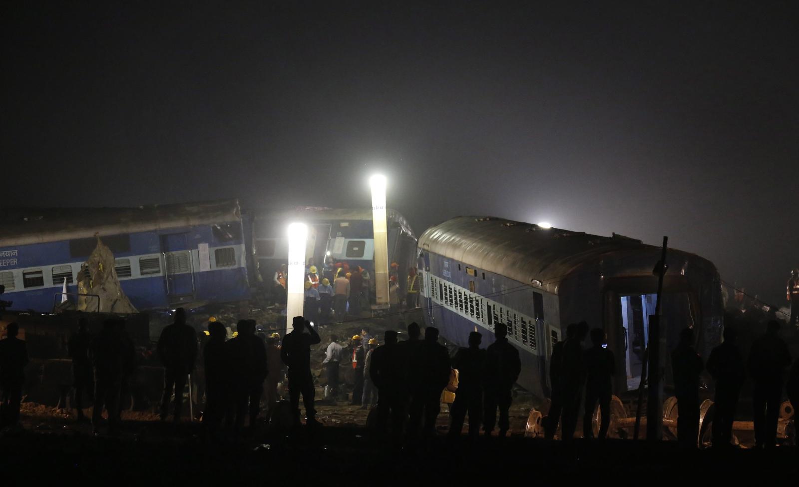 Robotnicy pracują w miejscu katastrofy pociągu w Indiach w której zginęło ponad 90 osób.