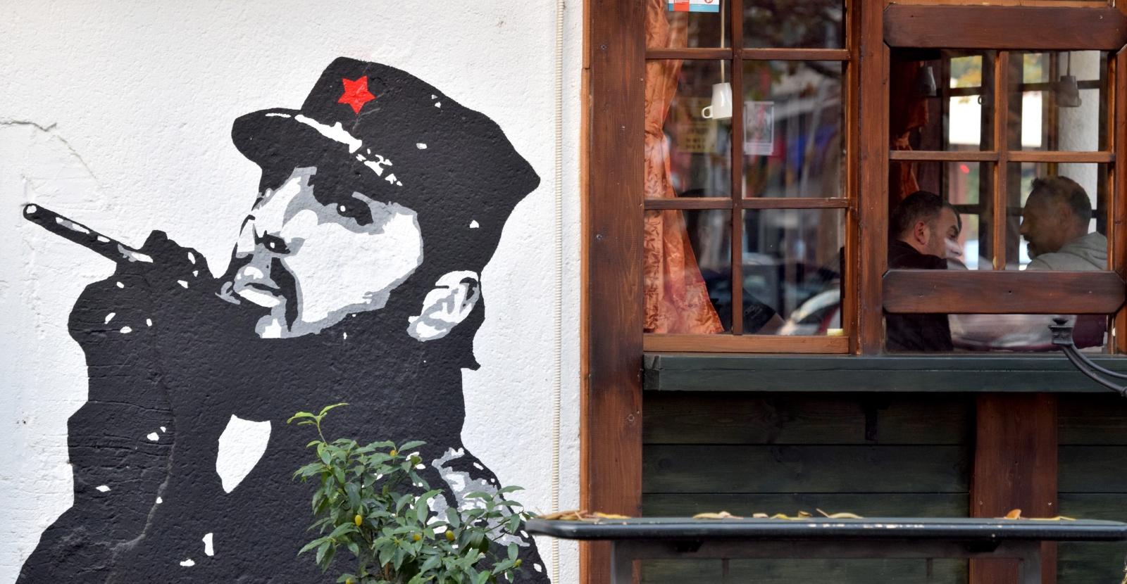 Ludzie siedzą w kawiarni obok murala z wizerunkiem zmarłego kubańskiego dyktatora, Podgorica, Montenegro.