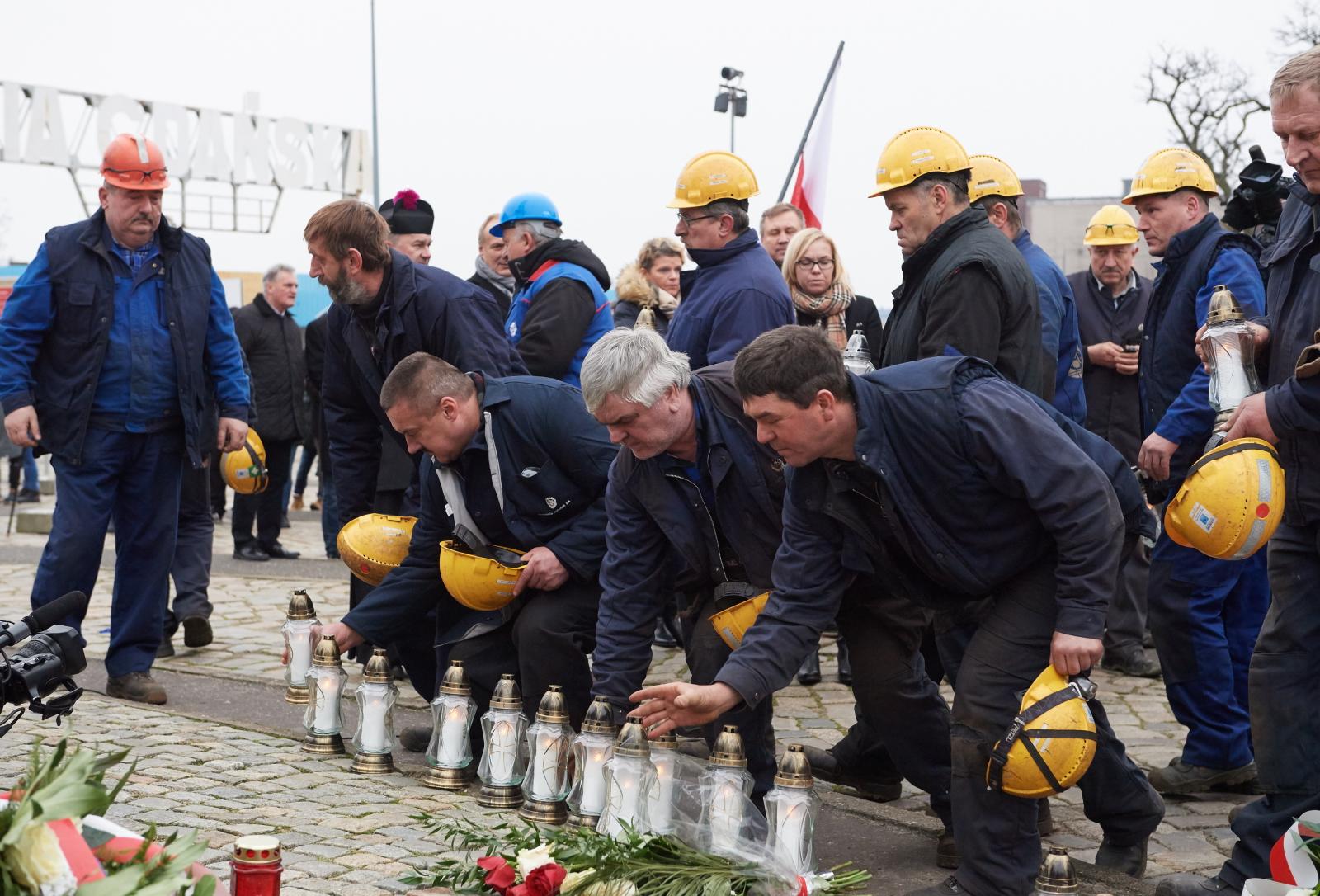 Stoczniowcy składają kwiaty i zapalają znicze przed Pomnikiem Poległych Stoczniowców podczas uroczystych obchodów 46. rocznicy Grudnia '70. Fot. PAP/Adam Warżawa