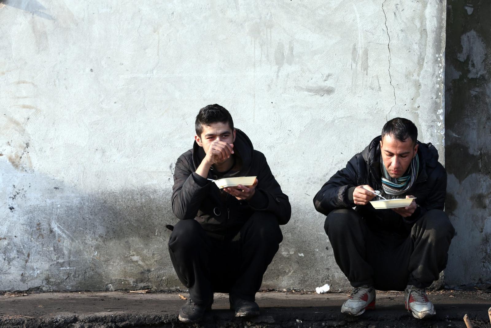 Migranci jedzący ciepły posiłek w Belgradzie. fot. EPA/KOCA SULEJMANOVIC