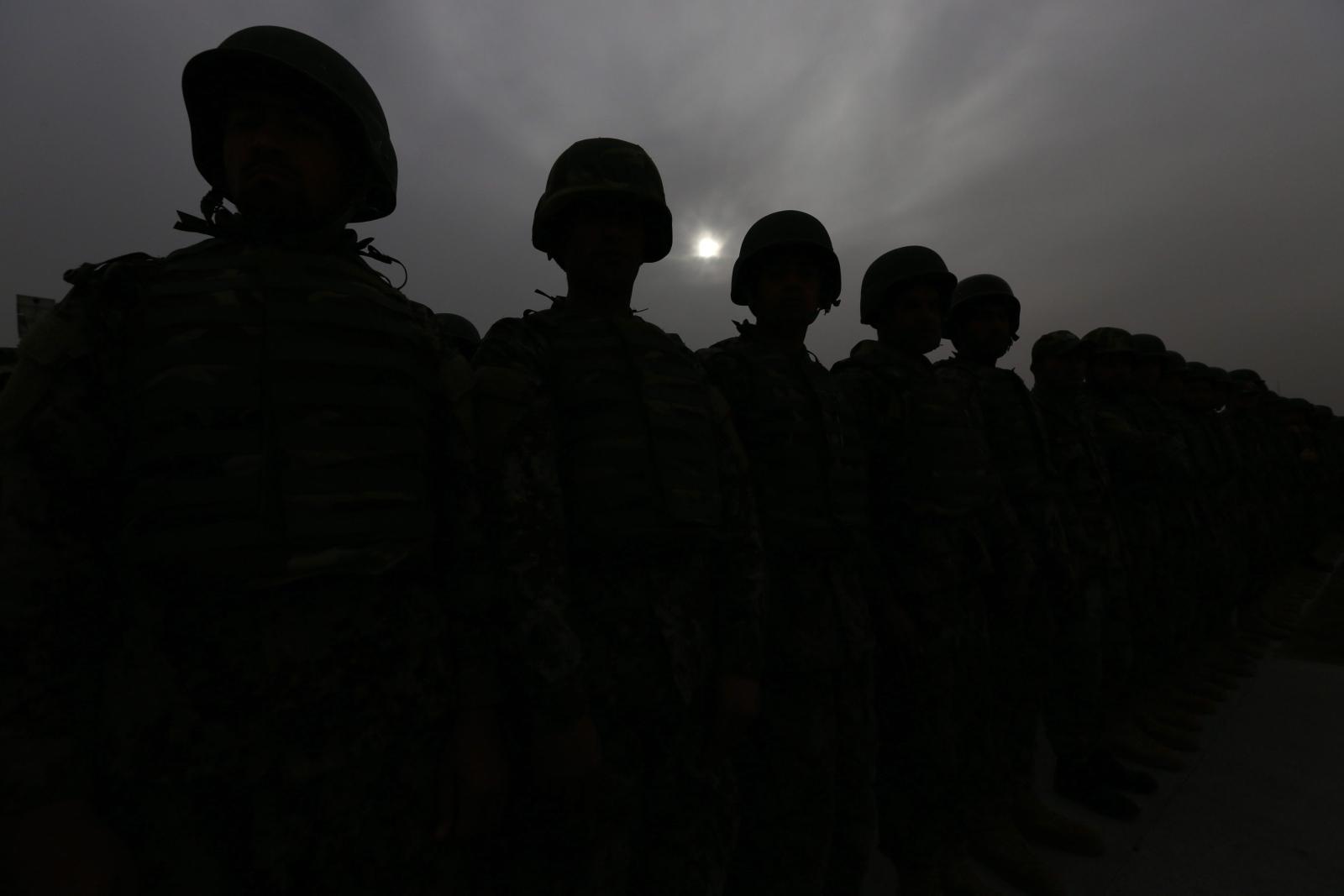 Sylwetki afgańskich żołnierzy biorących udział w uroczystości zmiany dowódcy.