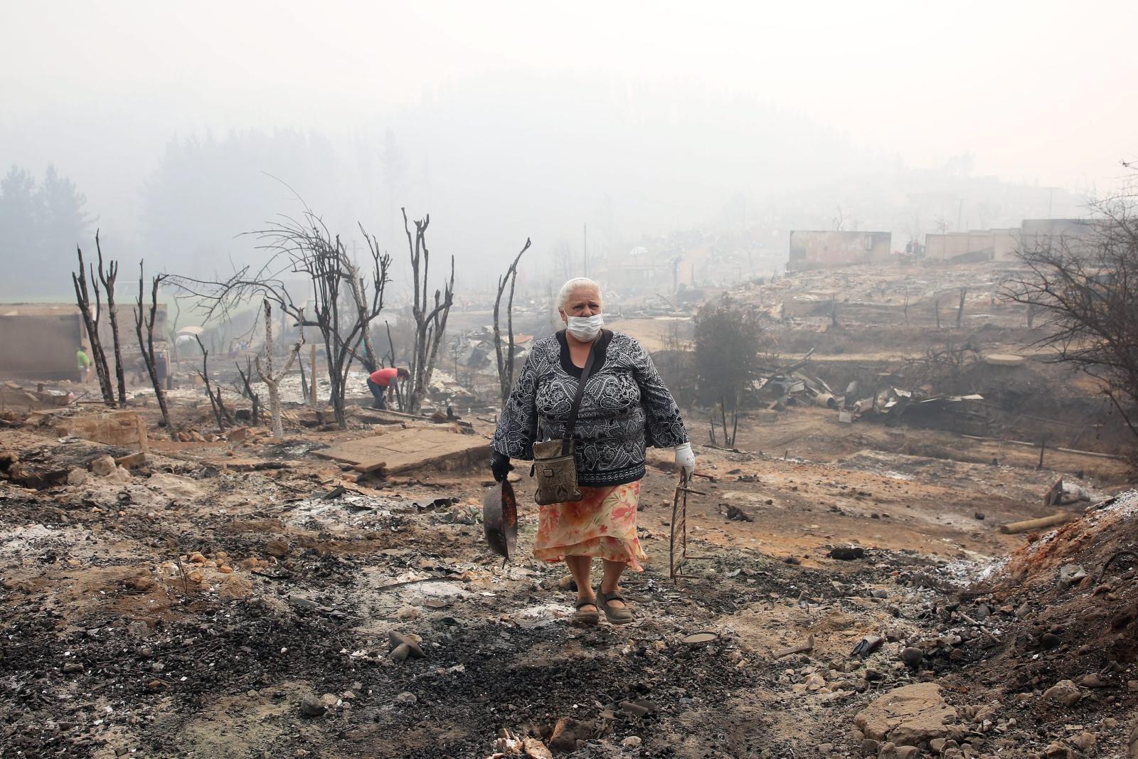 kobieta idzie przez ruiny domu spalonego w wielkim pożarze lasów w Chile.
