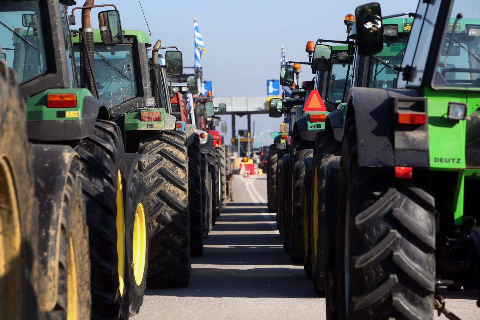 Protestujący greccy rolnicy tarasują autostradę traktorami.