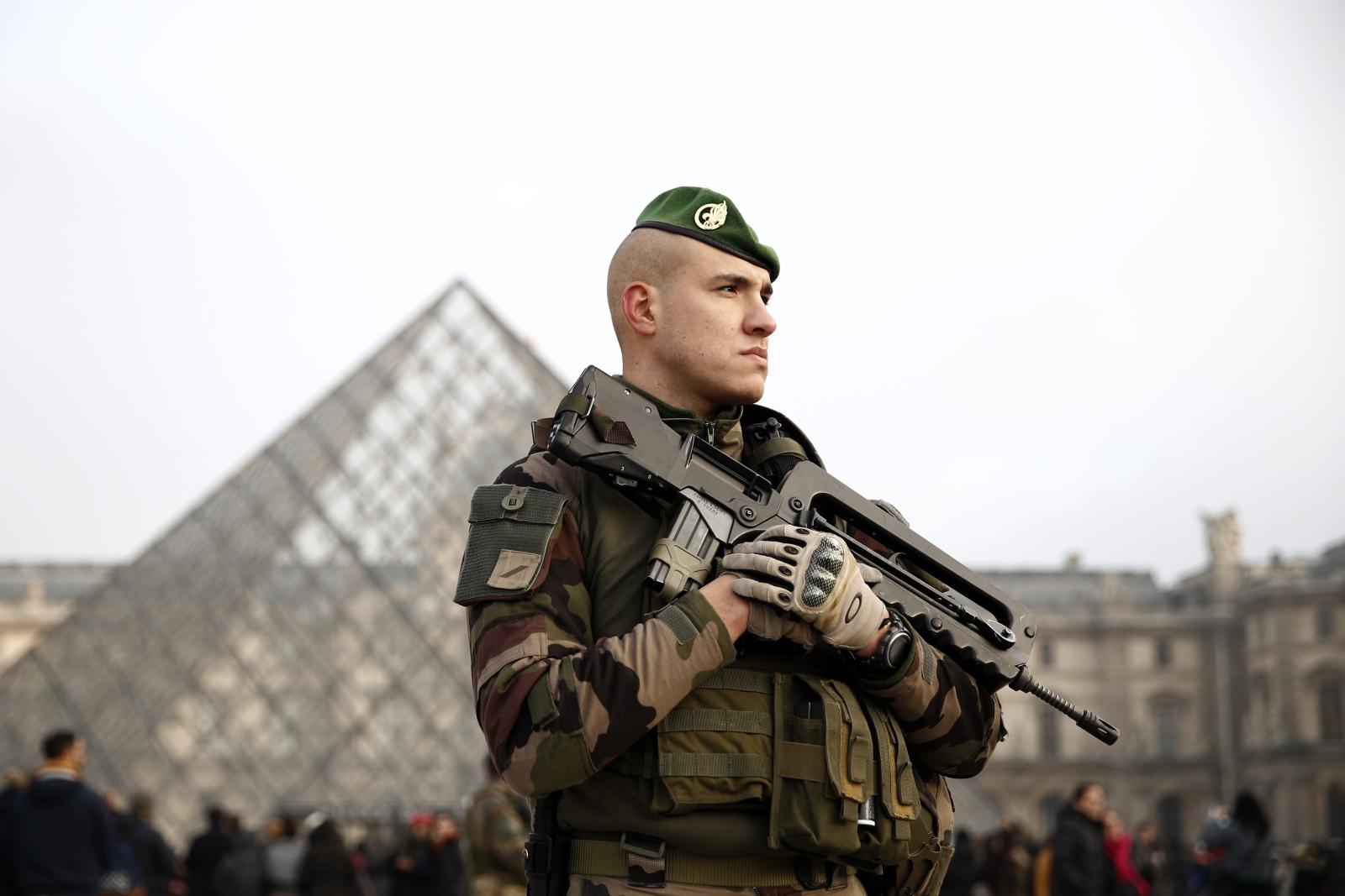 """Egipski napastnik uzbrojony w co najmniej jedną maczetę ruszył w kierunku czteroosobowego patrolu w pobliżu Luwru. Mężczyzna wykrzykiwał groźby i krzyczał """"Allah akbar"""". Żołnierz oddał do niego pięć strzałów. Napastnik został poważnie ranny w brzuch. Fot. PAP/EPA/YOAN VALAT"""