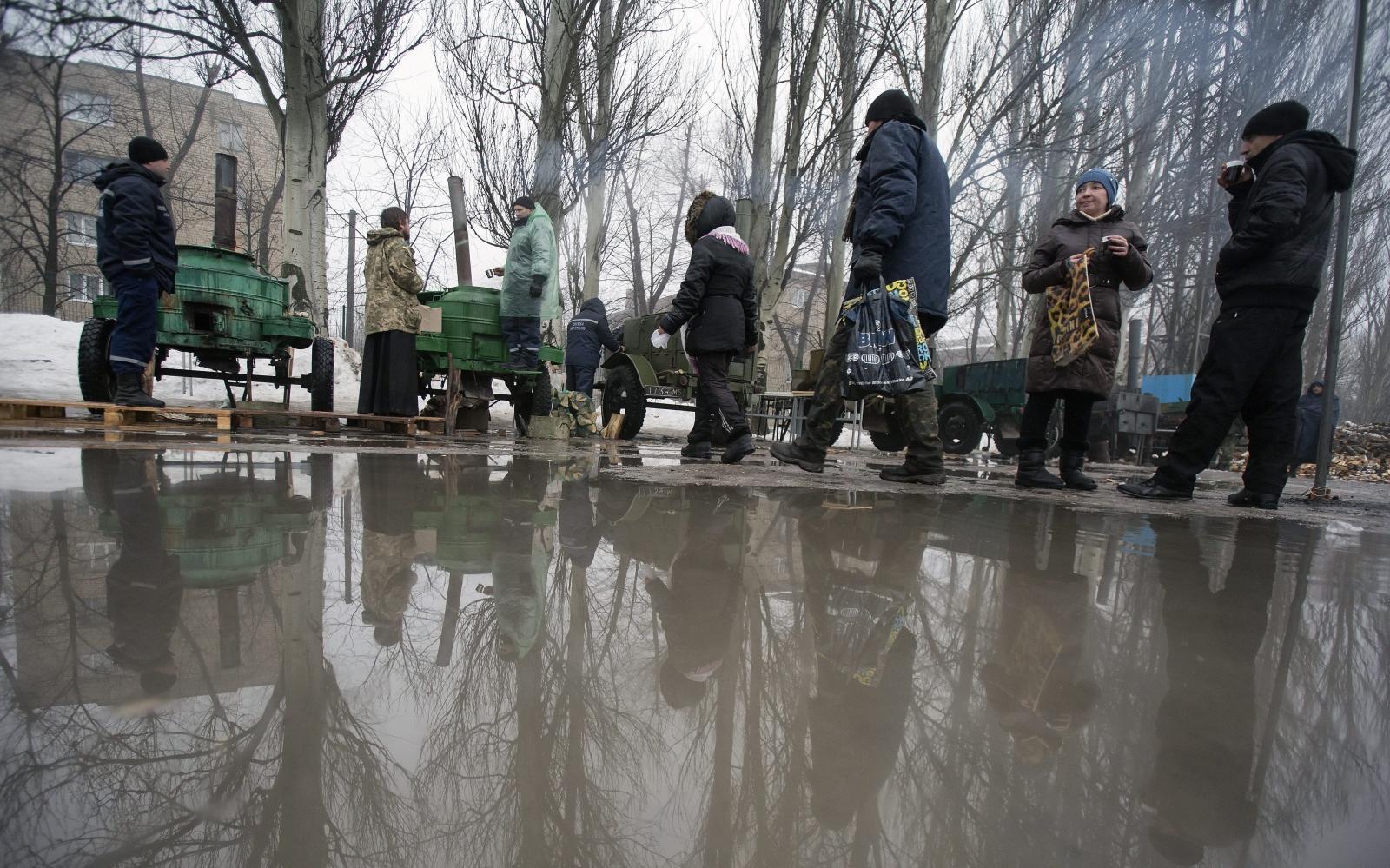 Mieszkańcy ustawiają się w kolejce po gorące jedzenie i picie rozdawane w Doniecku, Ukraina.