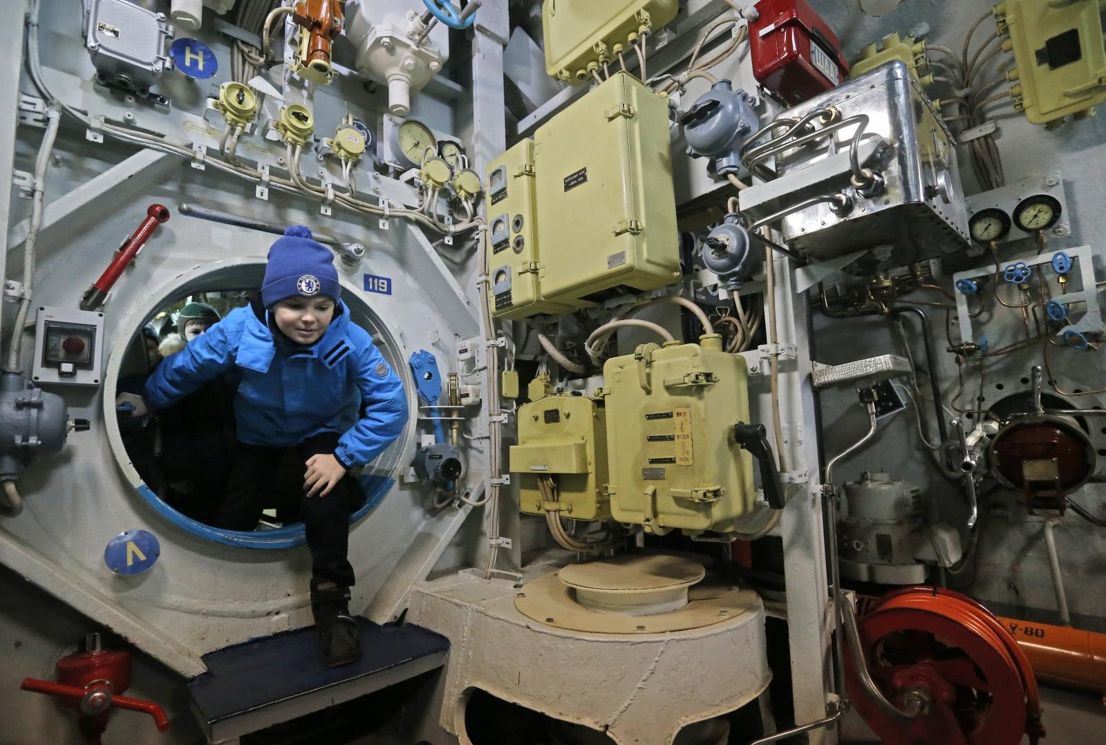 Chłopiec wchodzi do instalacji odwzorowującej wnętrze łodzi podwodnej w Muzeum Łodzi Podwodnych w Moskwie.