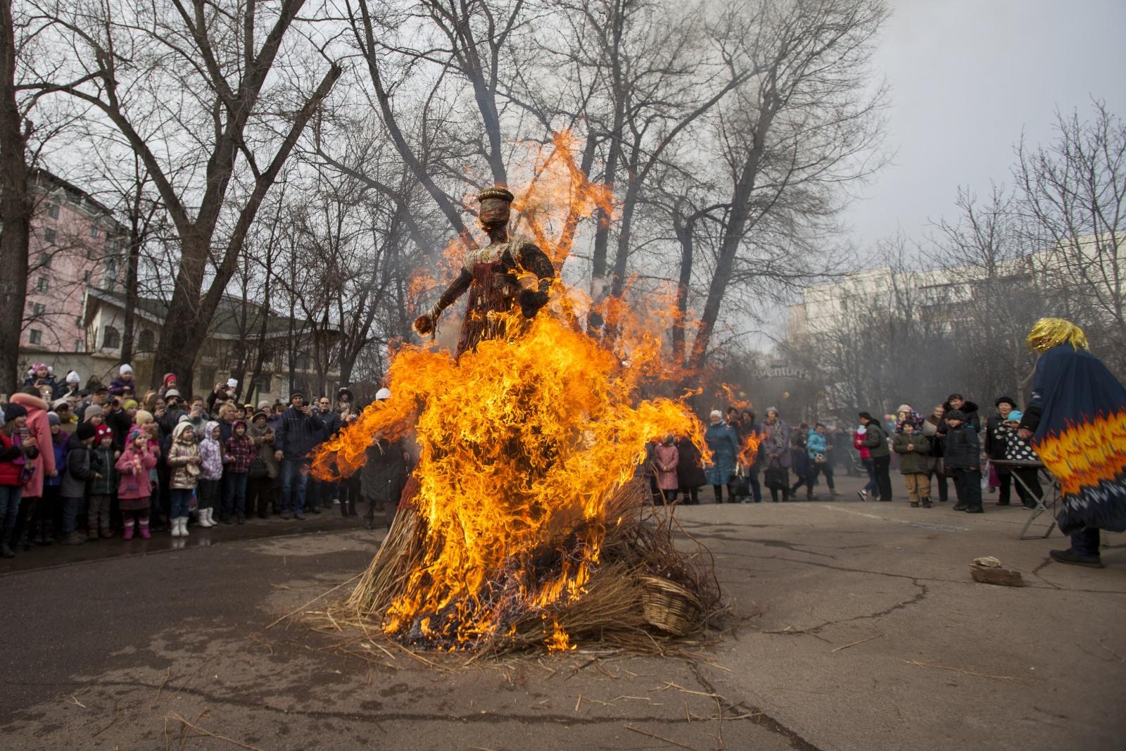 Ludzie oglądają spalenie kukły Pani Maslenitsa w siódmym i ostatnim dniu Tygodnia Naleśnika w Kiszyniowie, Mołdawia.