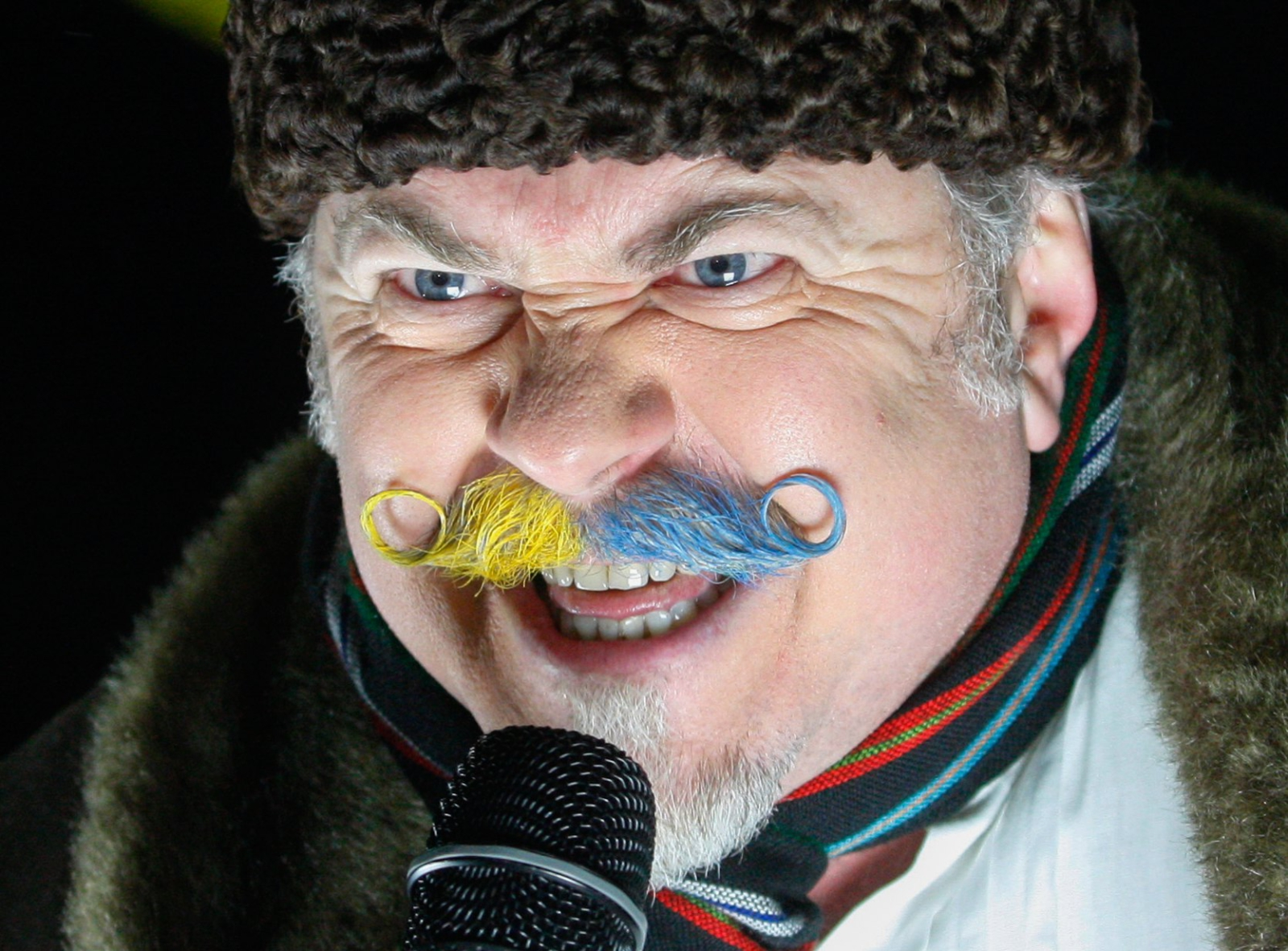 Aktywista z pomalowanymi na ukraińskie kolory wąsami przemawia podczas protestu pod rosyjską ambasadą w Kijowie, Ukraina.