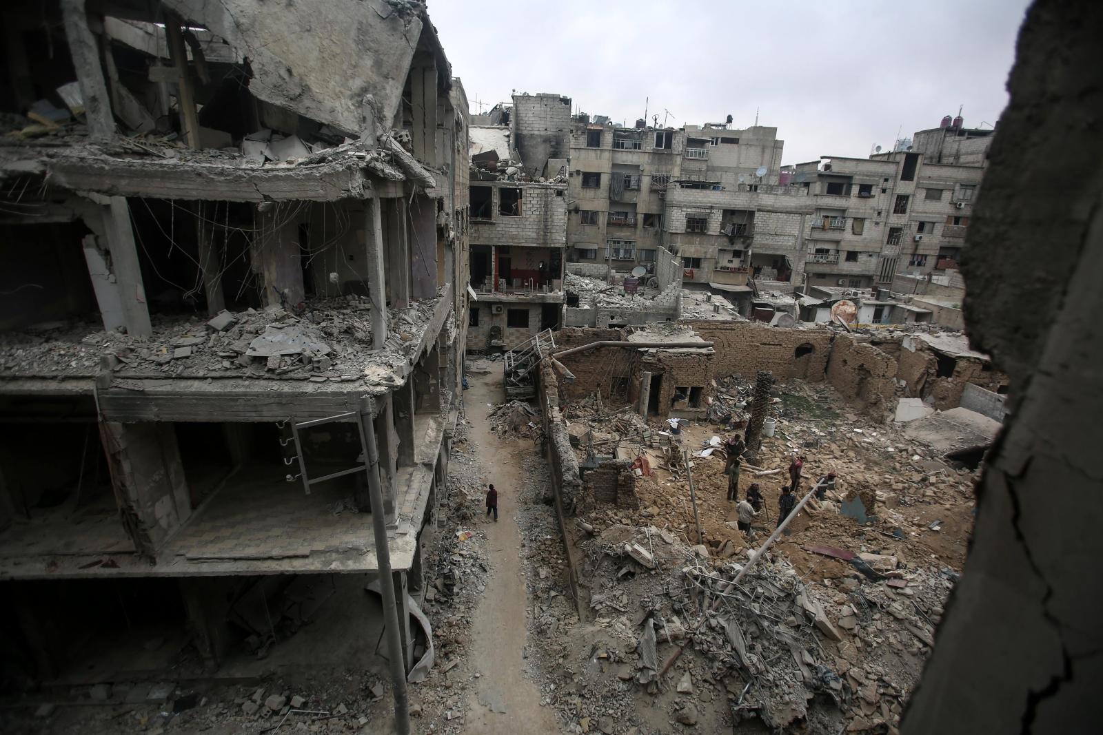 Ludzie szukają swoich rzeczy w zajętym przez rebeliantów mieście Duma, Syria.