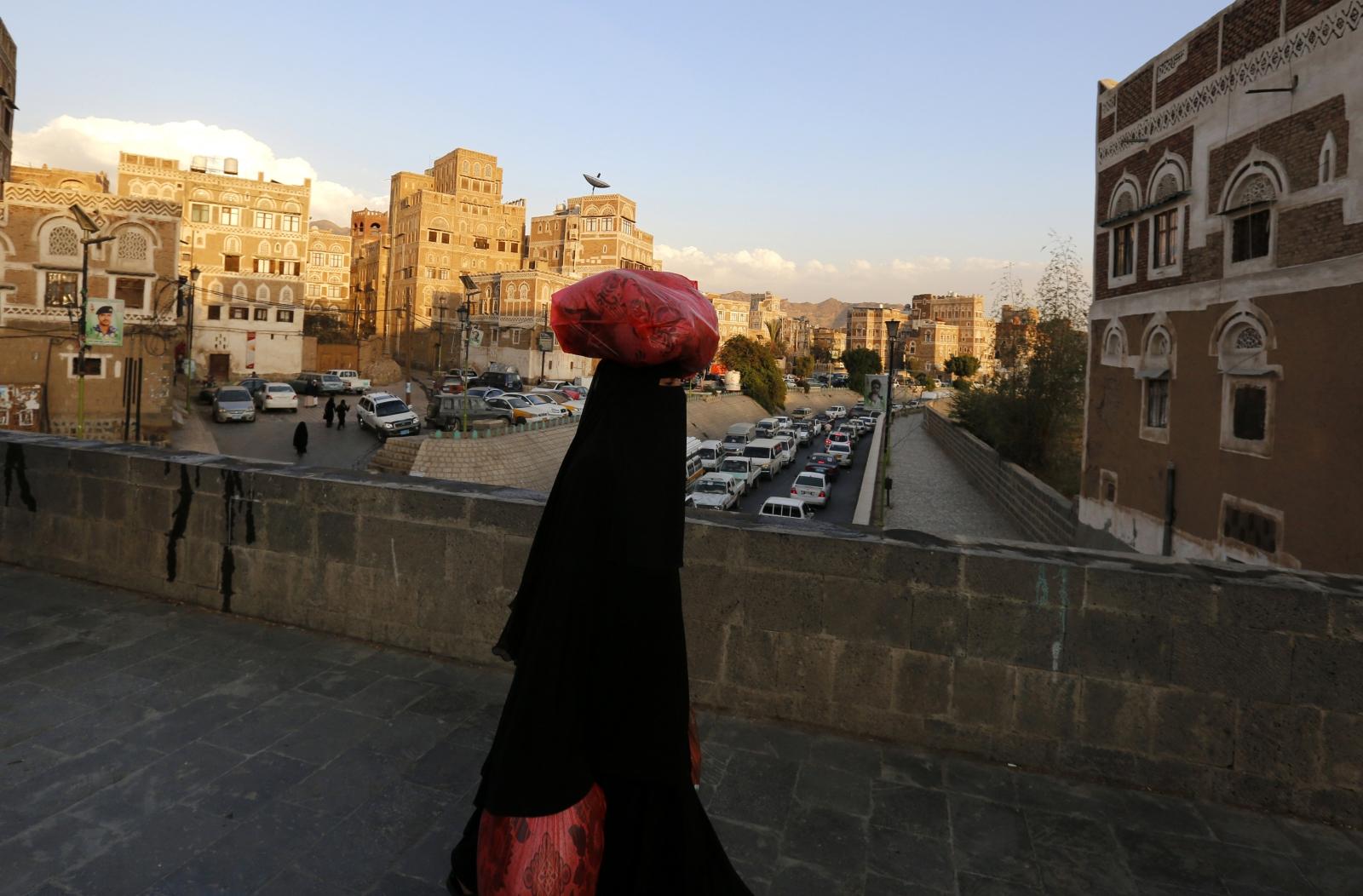 Jemeńska kobieta przechodzi przez obok zabytkowych budynków starej części Sany, Jemen.