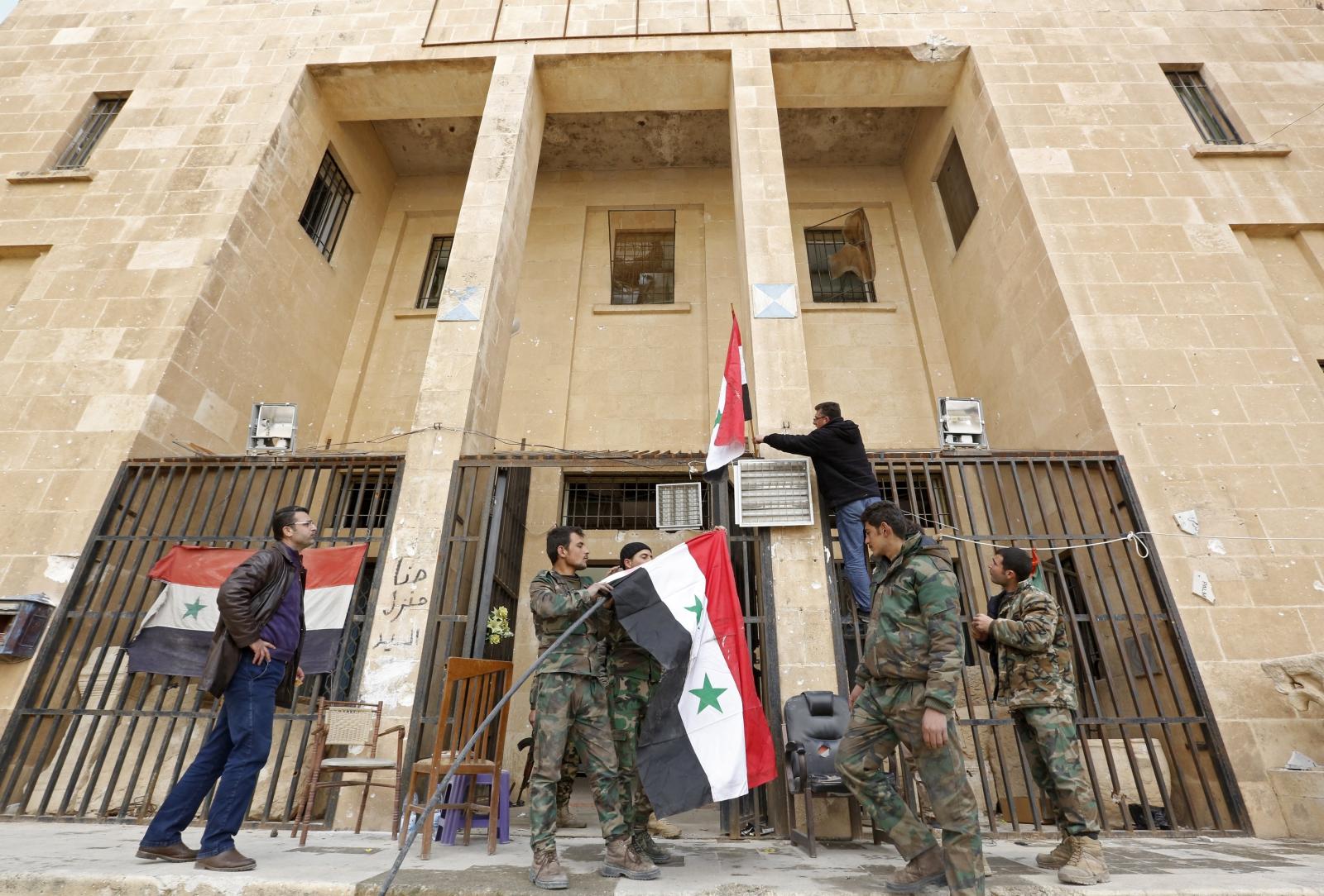 Syryjscy żołnierze wieszają flagi w odbitej z rąk dżihadystów Palmirze.