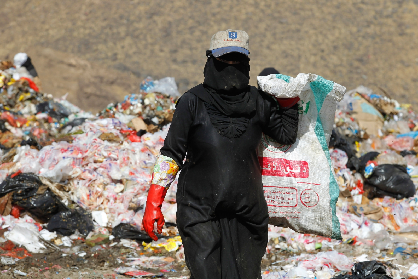 Jemeńska kobieta oczyszcza przedmioty nadające się do recyklingu na wysypisku śmieci na obrzeżach Sany, Jemen.