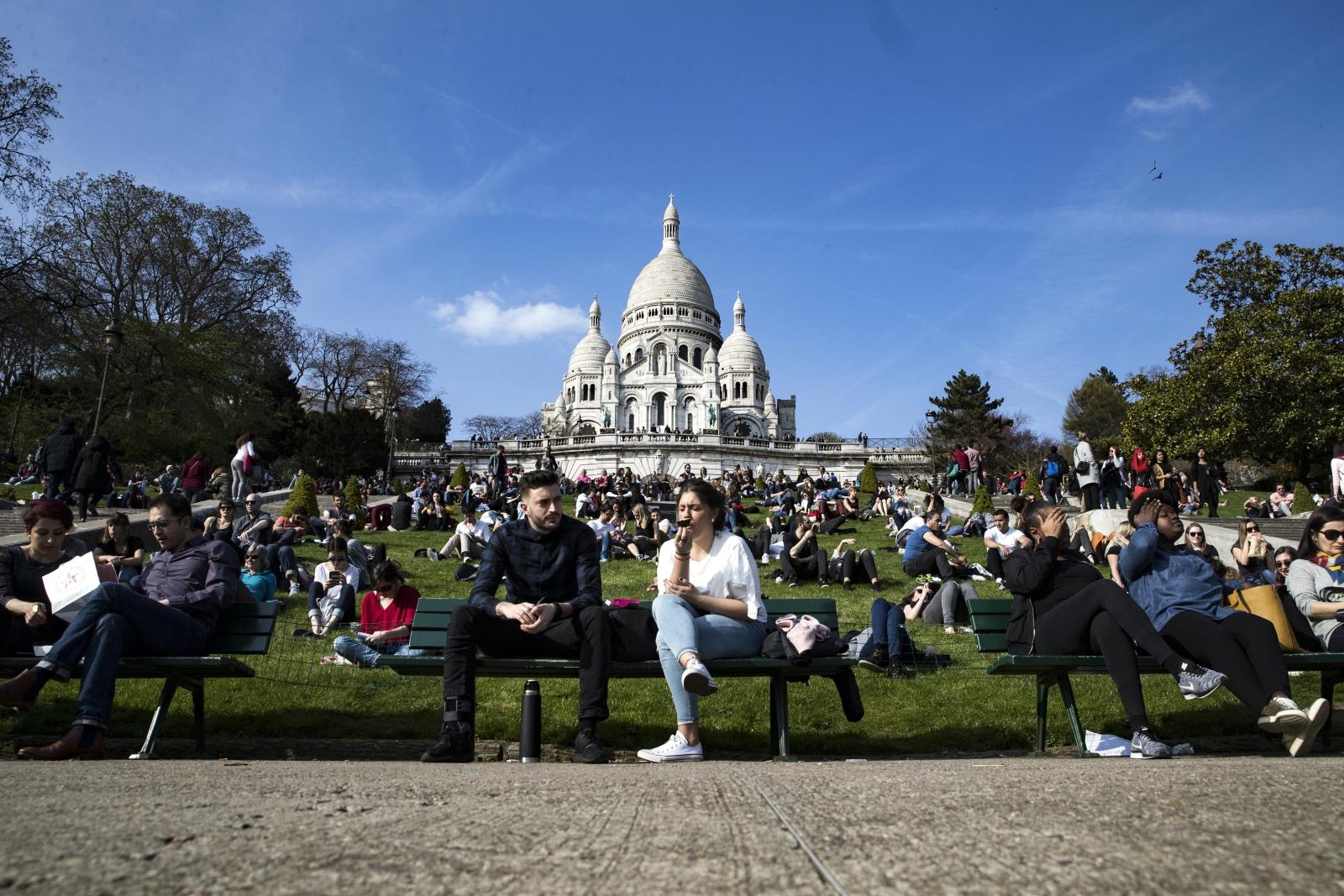 Ludzie wygrzewają się przy Sacre Coeur w Paryżu, Francja.
