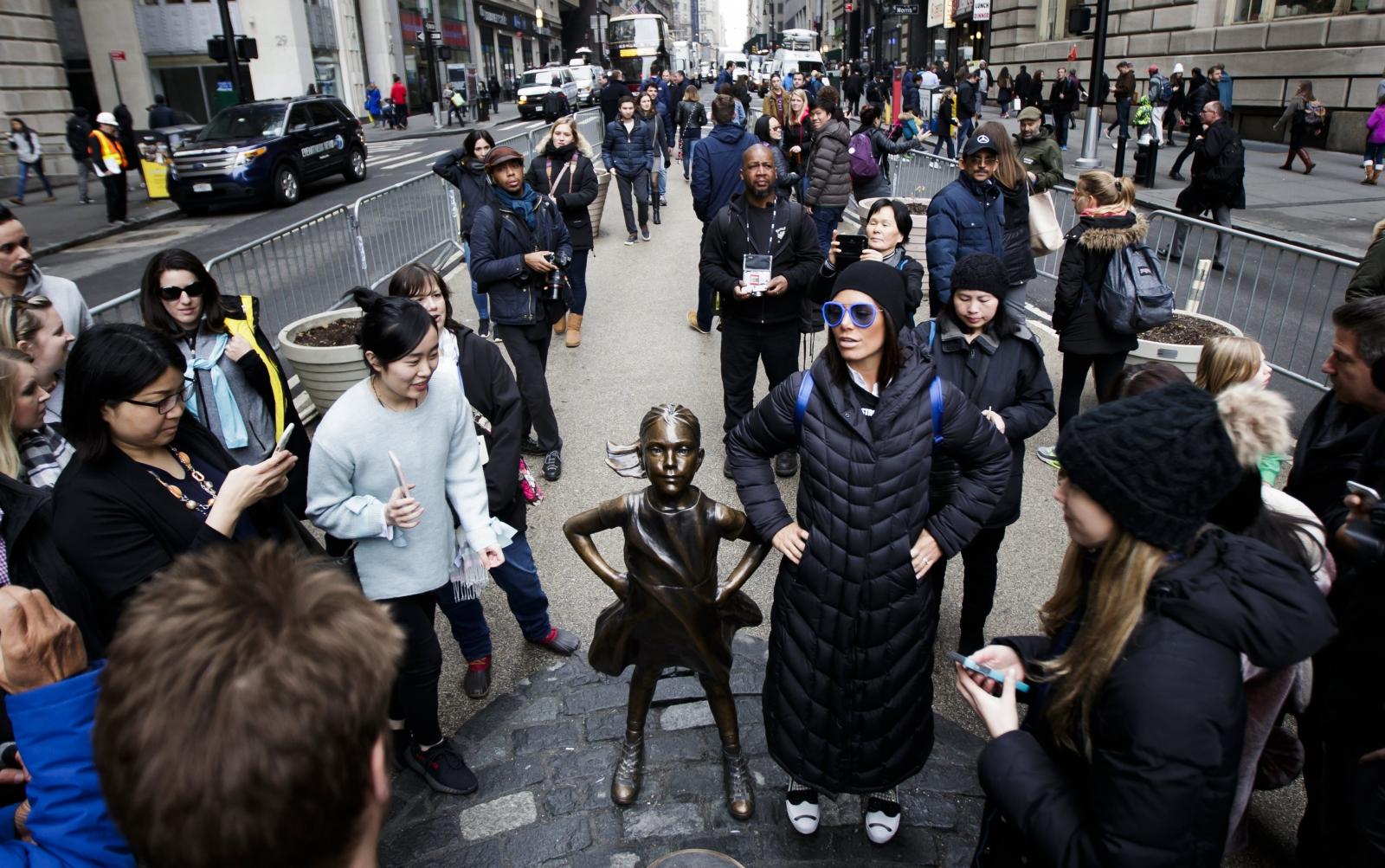 """Ludzie przyglądają się posągowi """"Nieustraszonej dziewczynki"""". Nowy Jork, Stany Zjednoczone."""