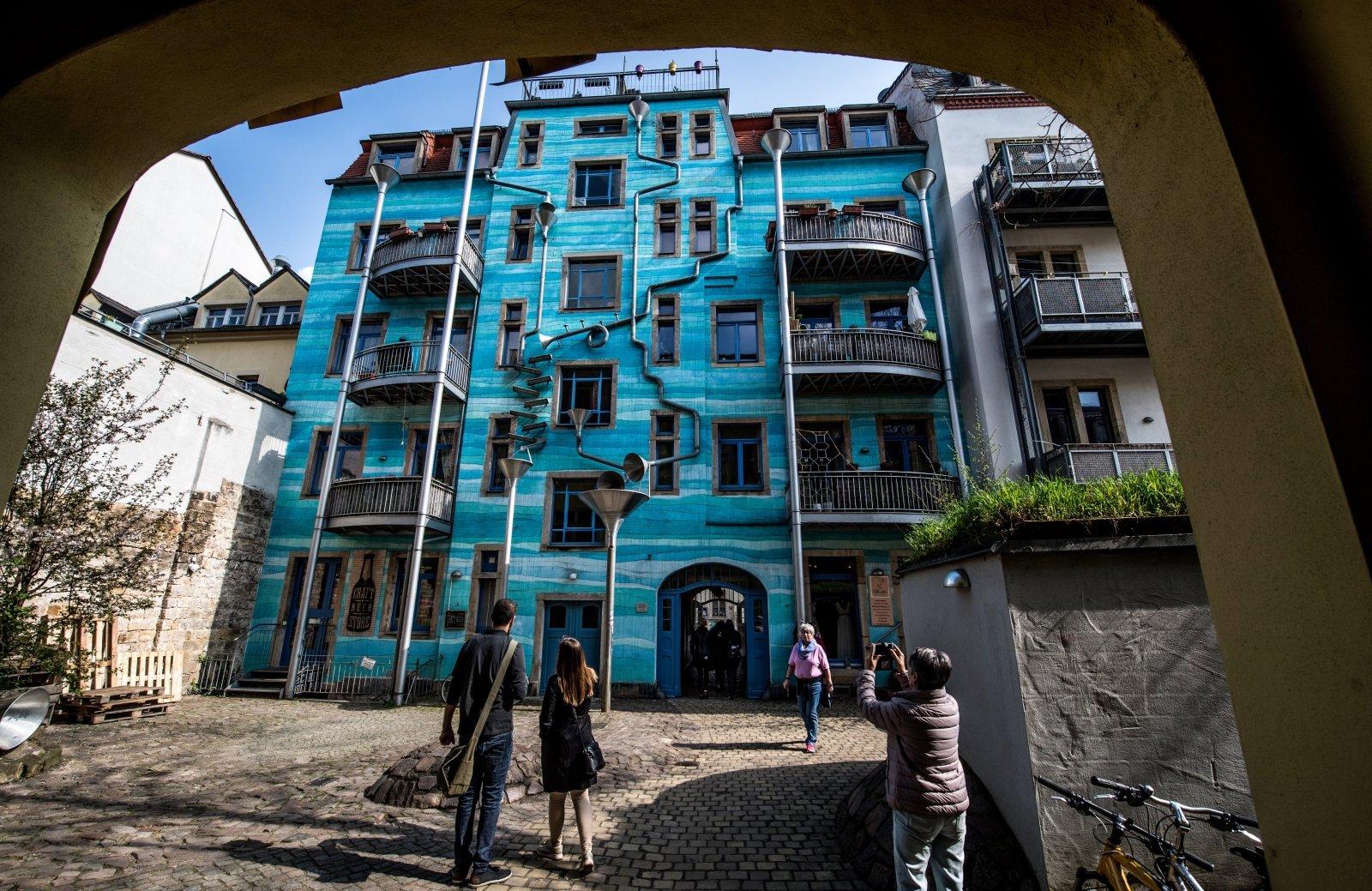 """Ludzie patrzą na """"Dziedziniec elementów"""" – muzyczny budynek w Neustadt, Drezno, Niemcy."""