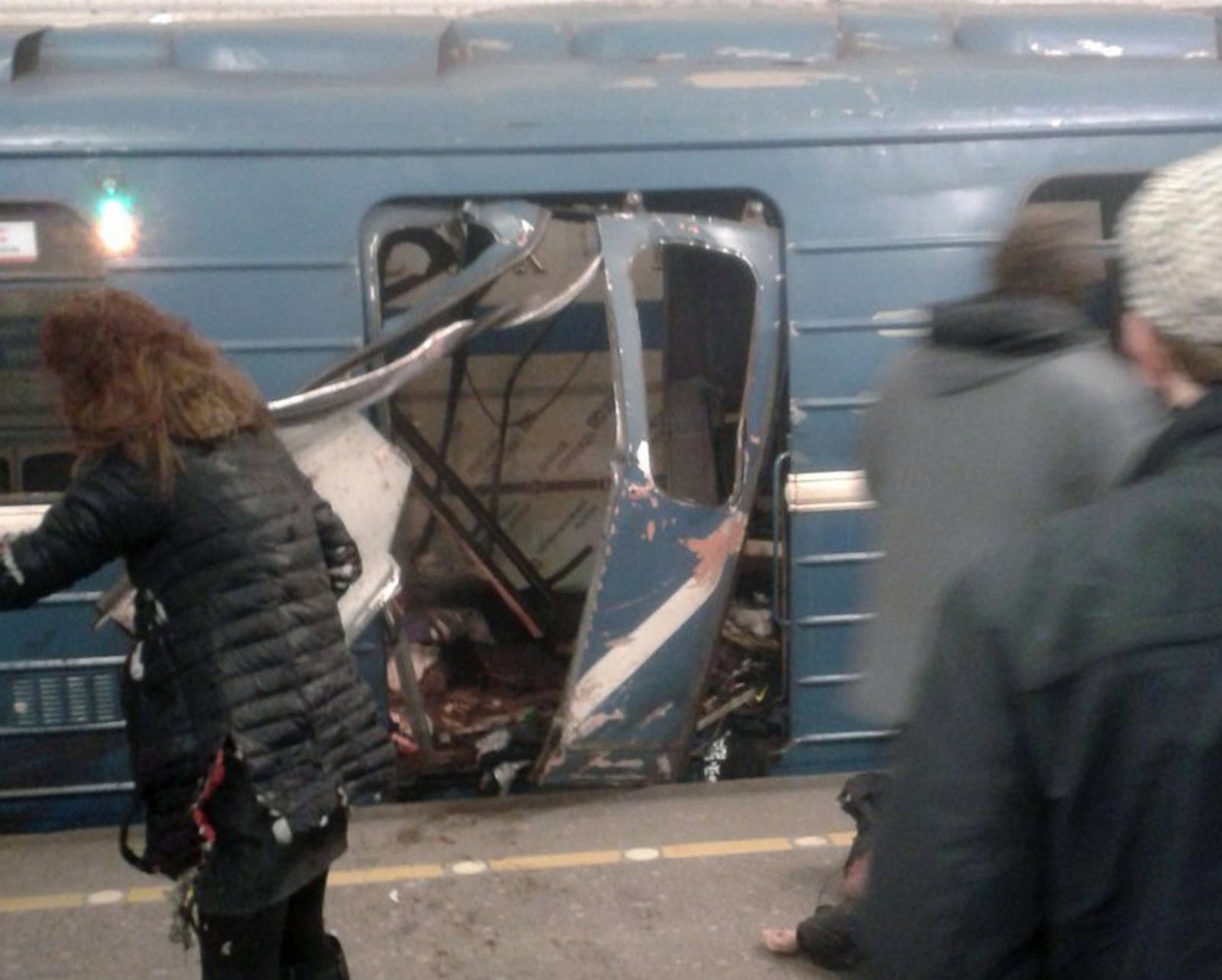 Ludzie przed zniszczonym w wybuchu pociągiem, Petersburg, Rosja.