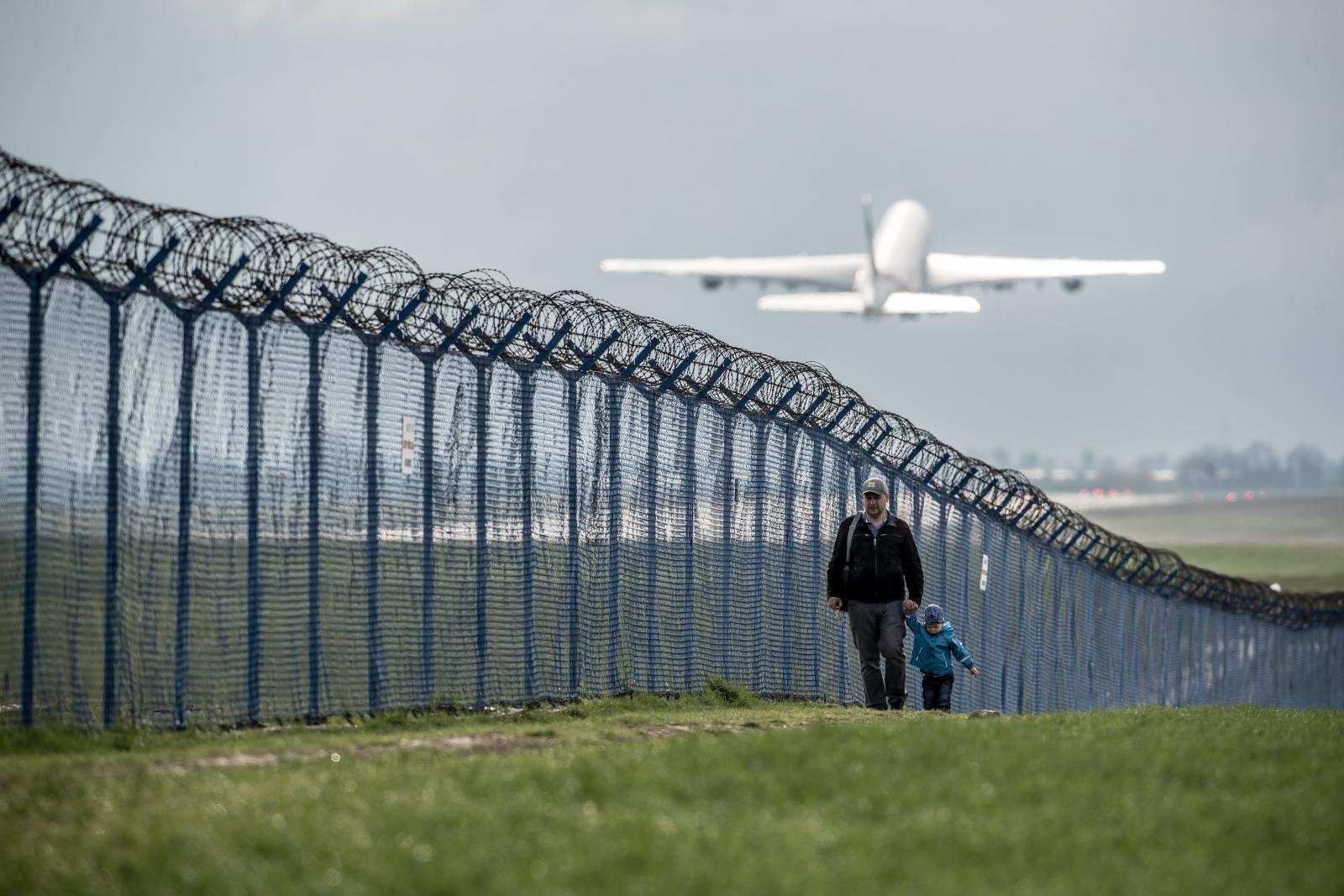 Chłopiec z synkiem przechadzają się obok lotniska im. Vaclava Havla, Praga, Czechy.