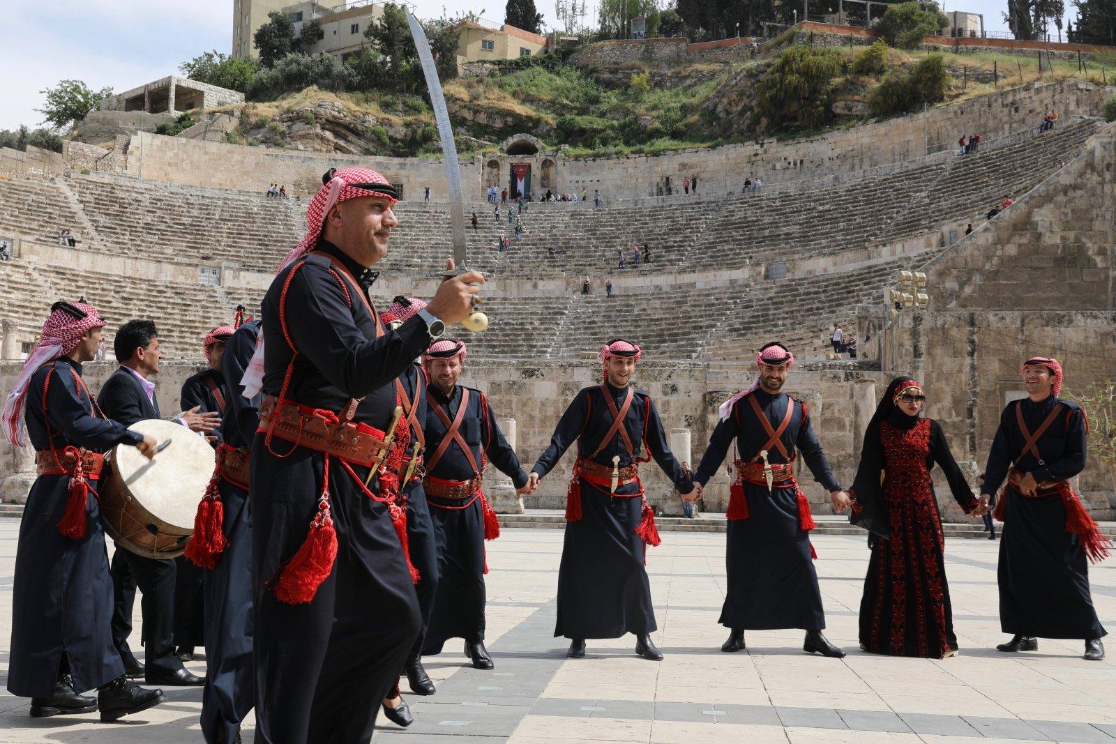 Jordańscy tancerze naprzeciwko rzymskiego teatru w Ammanie promują Middle East Peace Tour.