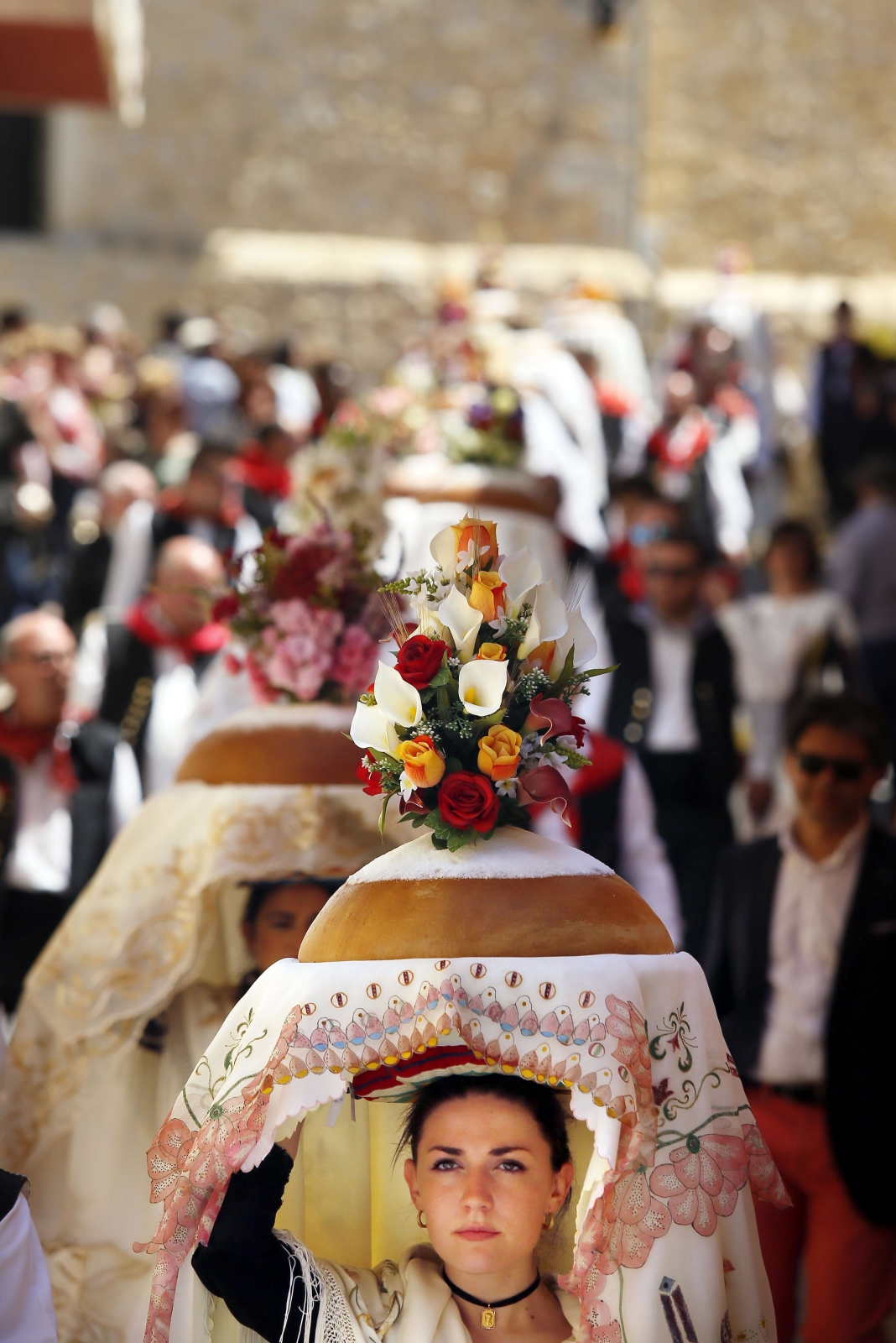 Kobiety ubrane w tradycyjne stroje kultywują starą hiszpańską tradycję niosąc na głowie pobłogosławiony chleb w darze dla św. Grzegorza w Torremanzanas, Hiszpania.