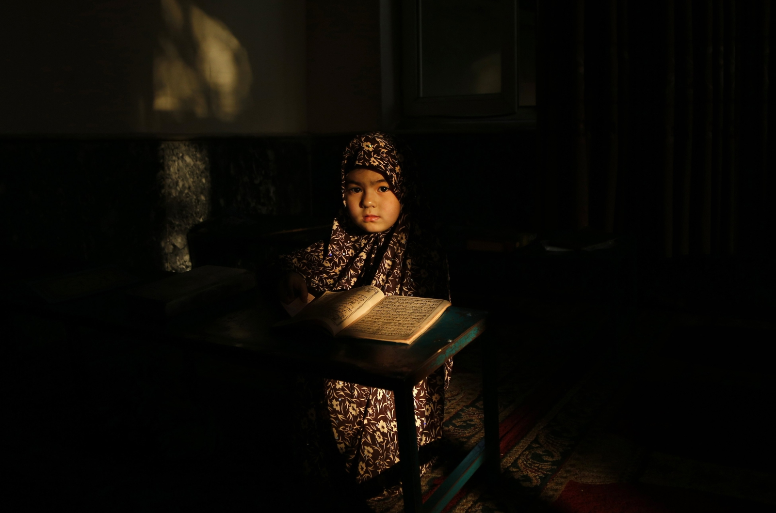 Afgańska dziewczynka czyta Koran w trakcie świętego miesiąca Ramadanu, Kabul, Afganistan.