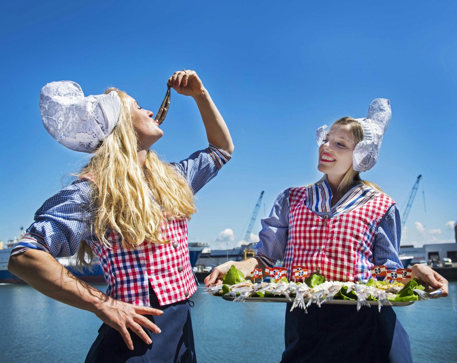 Holenderki, jedzące narodowy przysmak - tradycyjne śledzie.