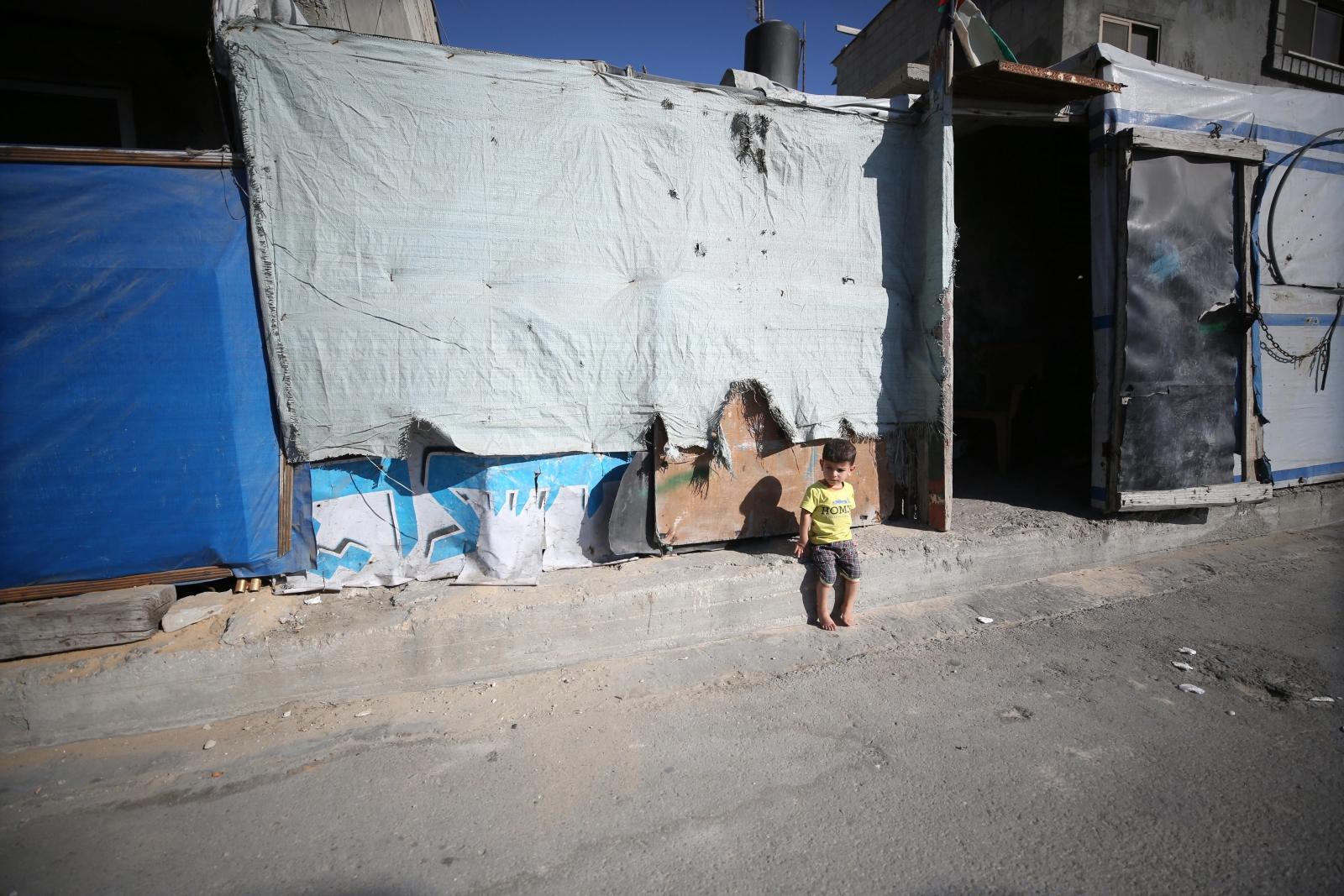 Palestyński uchodźca siedzi przed swoim domem w obozie uchodźców Deir Al Balah w strefie Gazy.