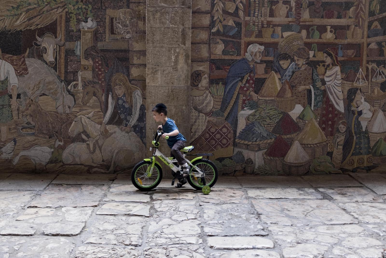 Mały ortodoksyjny Żyd jeździ na rowerze w żydowskiej części Starego Miasta Jerozolimy.