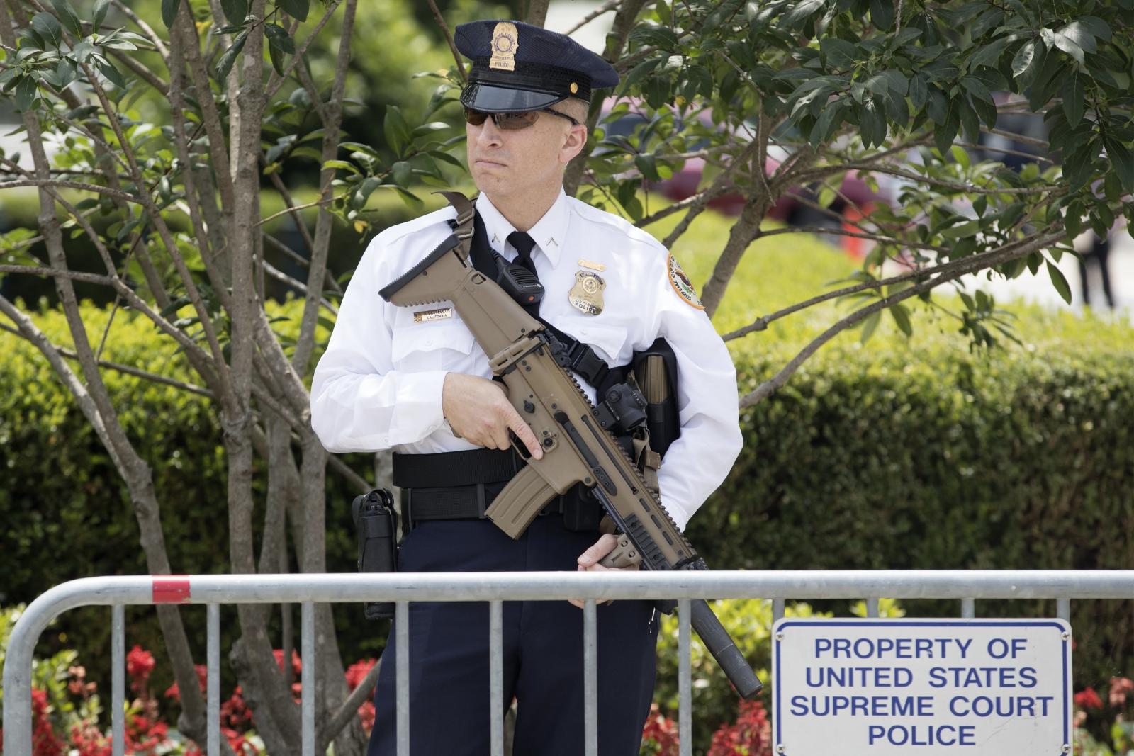Policjant pełniący rolę strażnika stoi z bronią przez budynkiem Sądu Najwyższego, USA.