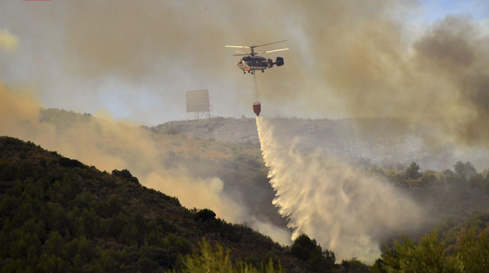 Helikopter gasi pożar lasu w Walencji, Hiszpania.
