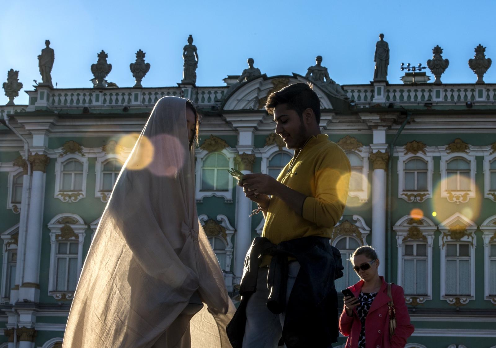 Ludzie korzystają z dobrej pogody na placu przed Narodowym Muzeum Ermitażu w Sankt Petersburgu.
