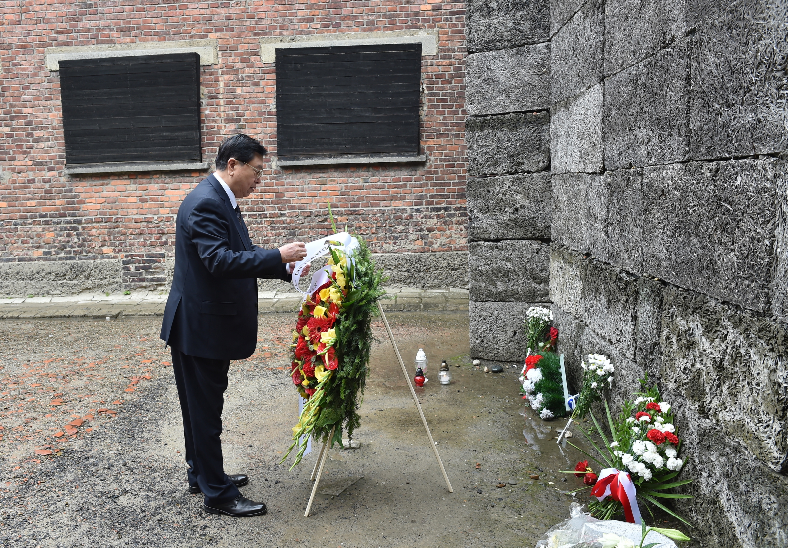 Przewodniczący Stałego Komitetu Ogólnochińskiego Zgromadzenia Przedstawicieli Ludowych Zhang Dejiang złożył kwiaty przy Ścianie Śmierci na terenie byłego niemieckiego, nazistowskiego obozu koncentracyjnego i zagłady KL Auschwitz w Oświęcimiu, Fot.  PAP/Jacek Bednarczyk