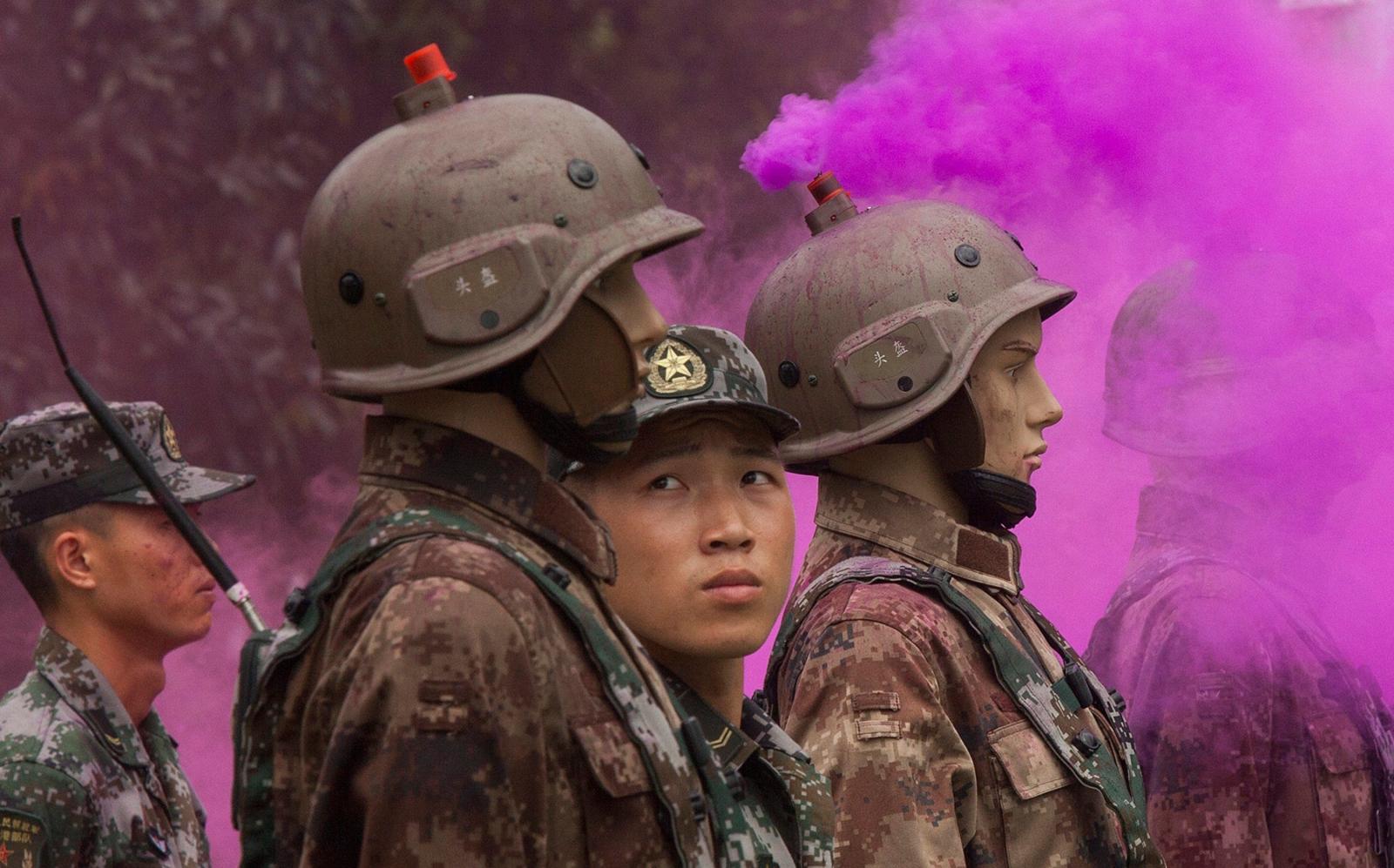Żołnierz Chińskiej Armii Ludowo-Wyzwoleńczej patrzy na figury żołnierzy.