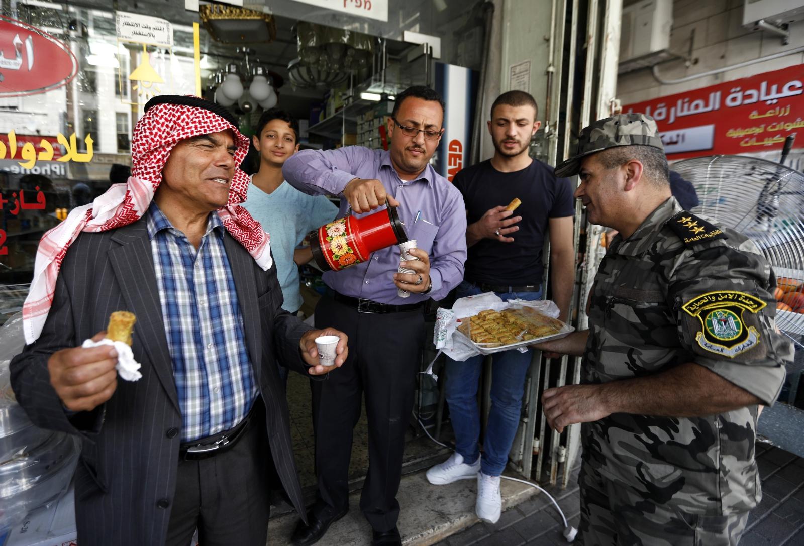 Palestyński żołnierz częstuje ludzi na ulicy słodyczami