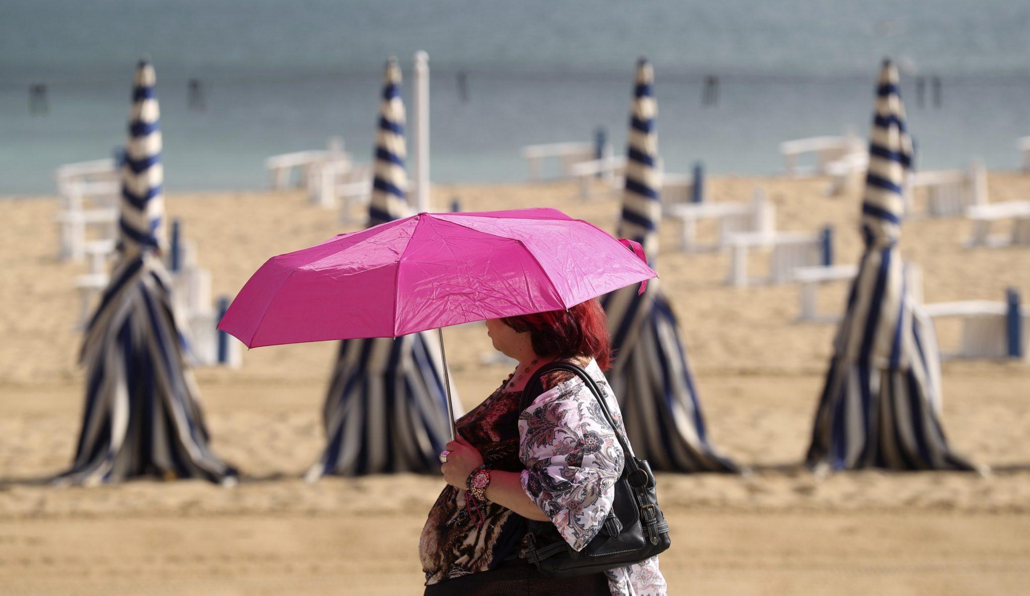 Kobieta z parasolką w czasie upałów na plaży Ondaretta w San San Sebastian, w północnej Hiszpanii , fot: Juan Herrero PAP/EPA.