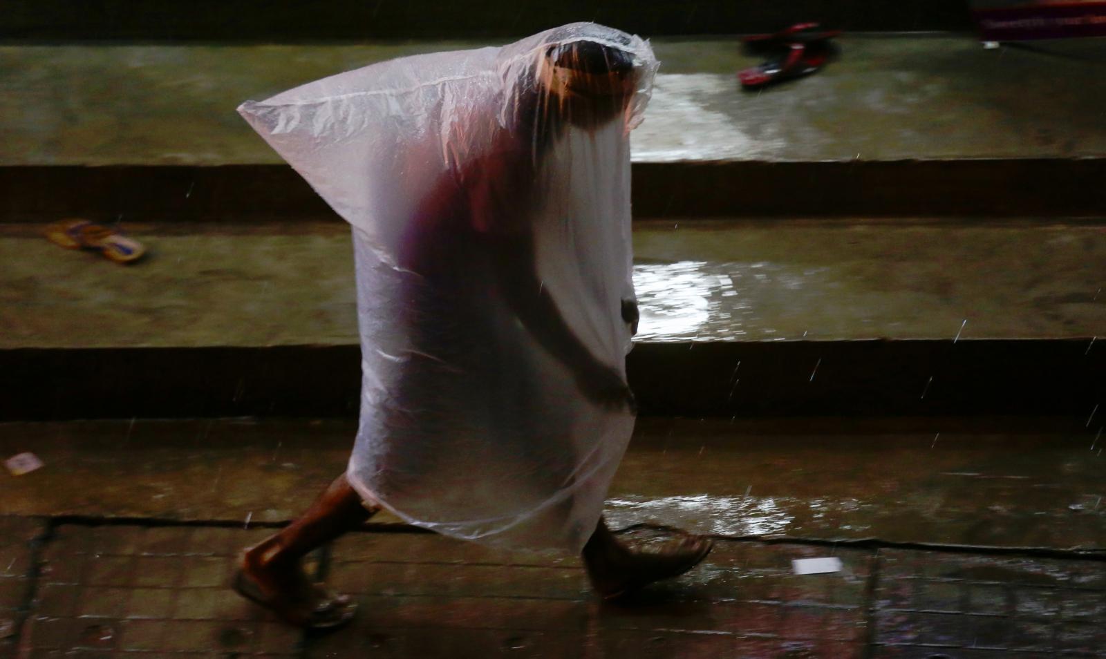 Kobieta chroniąca się przed deszczem pod plastikowym workiem, Bengaluru, Indie.