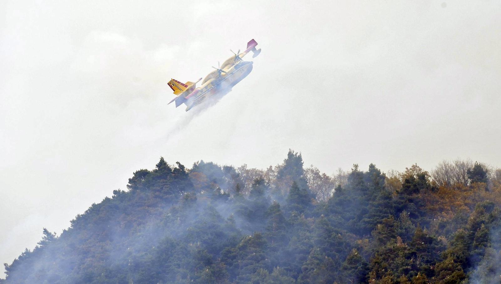 Samolot pomaga przy rozprzestrzeniającym się ogniu. Region Val di Susa pod Turynem, Włochy.