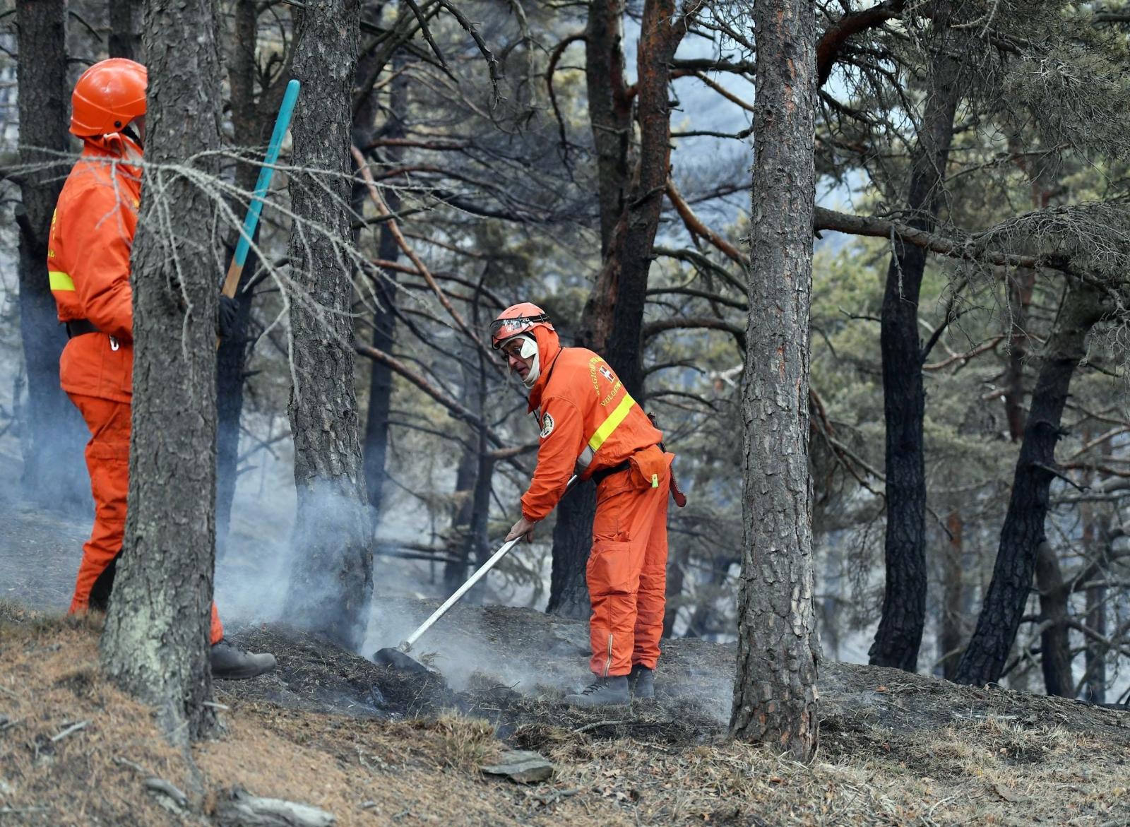 Wolontariusze pomagają przy rozprzestrzeniającym się ogniu. Region Val di Susa pod Turynem, Włochy.