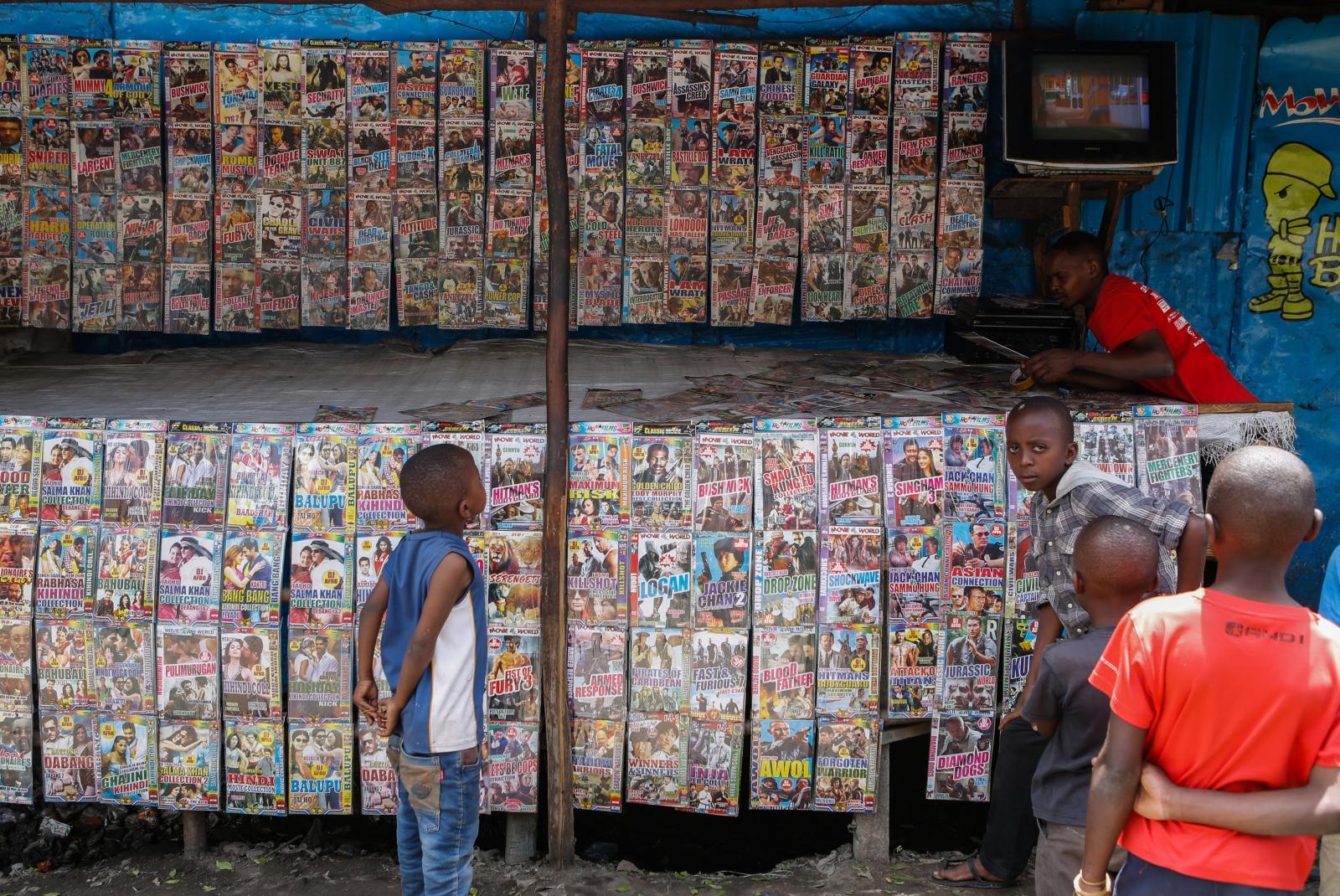 Dzieci patrzą na uliczny kiosk z setkami filmów fabularnych w Nairobi, Kenia.