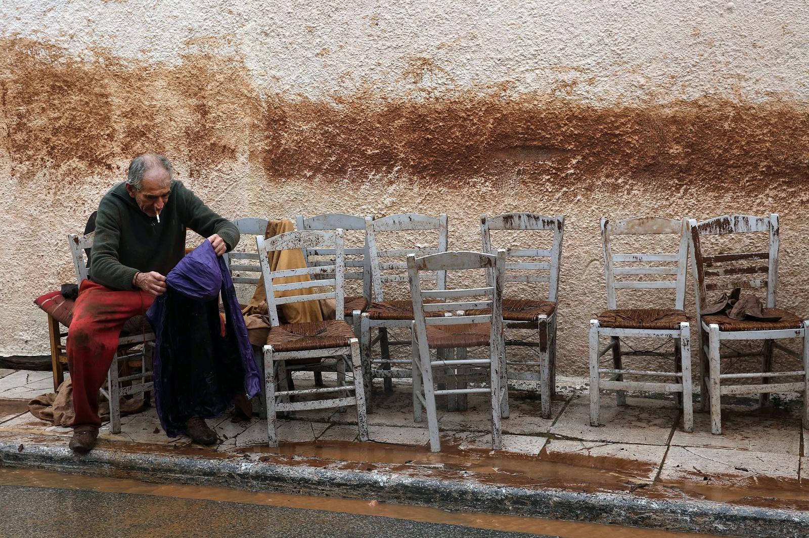 Mężczyzna próbuje wysuszyć ubrania na ulicy Mandry w Grecji. W kraju trwają ogromne powodzie.