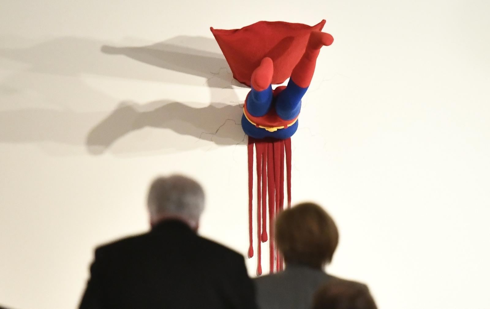 Angela Merkel przechodzi wokół ciekawego dzieła artystycznego, czyli wbitego w ścianę Supermana. Rezydencja Baden Wuerttemberg w Berlinie, Niemcy.
