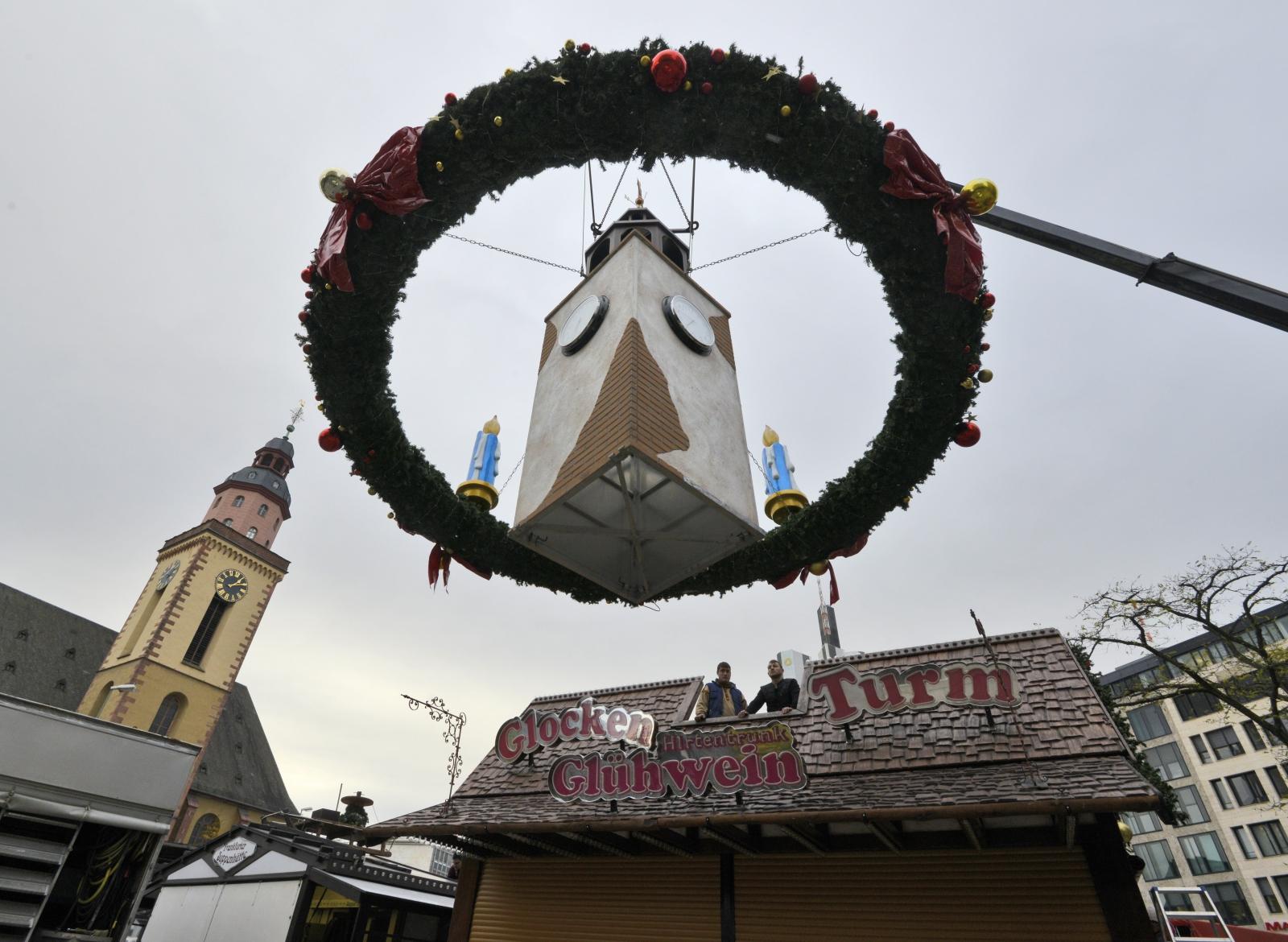 Robotnicy montują miniaturową wieżę zegarową jako bożonarodzeniową ozdobę rynku we Frankfurcie, Niemcy.