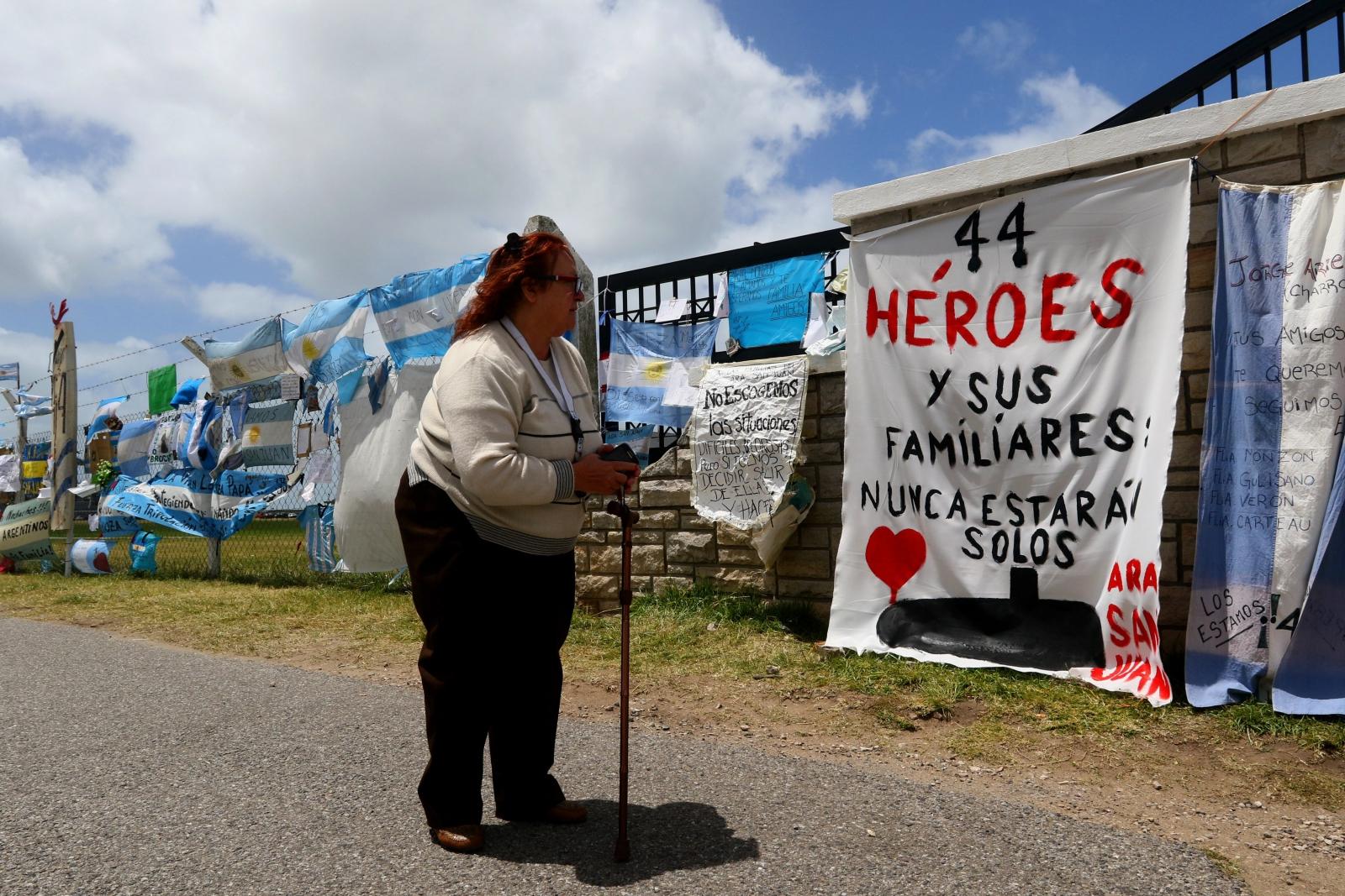 Kobieta wpatruje się w baner poświęcony załodze zaginionej argentyńskiej łodzi podwodnej.