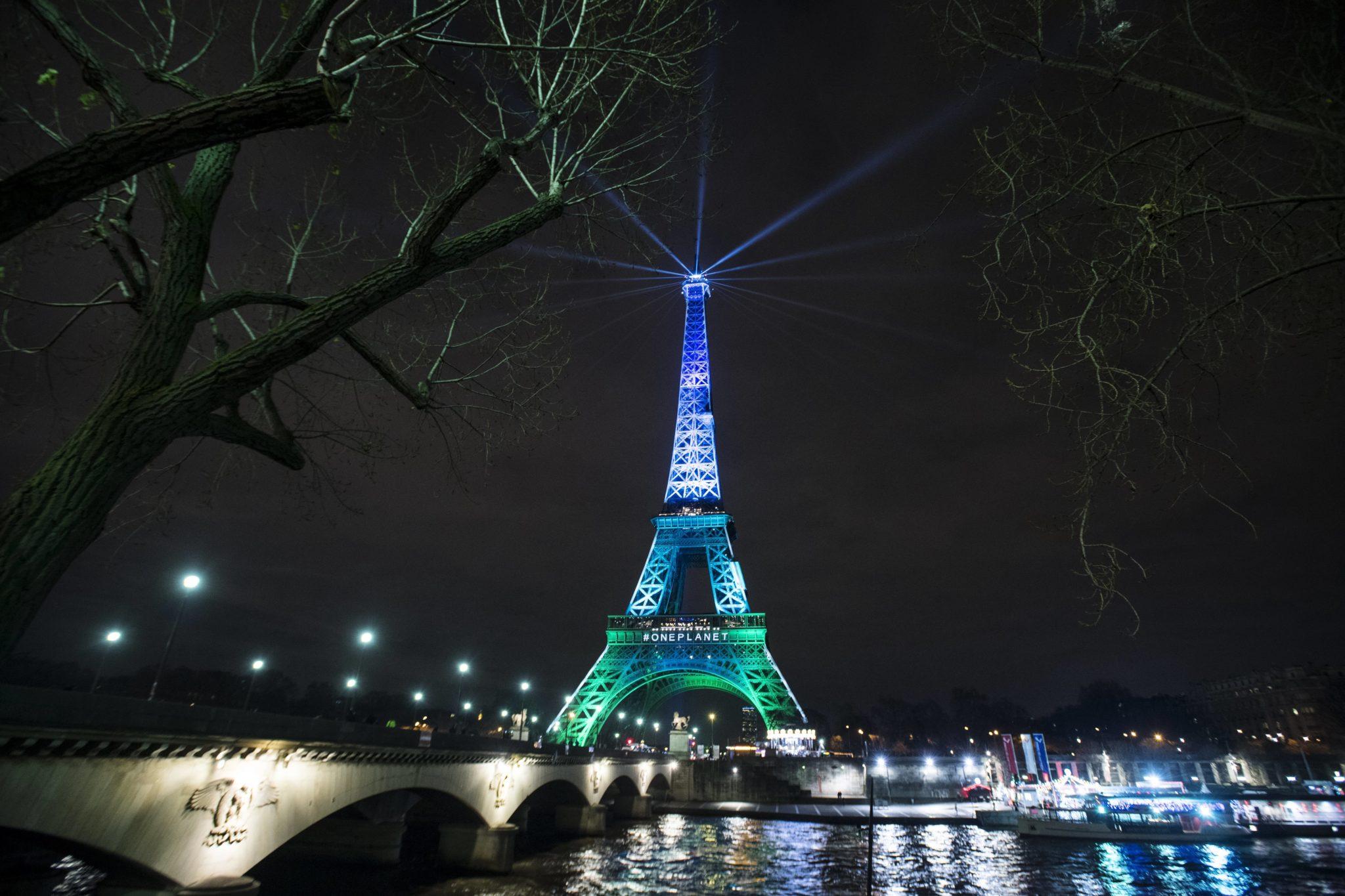 Francja: Wieża Eiffla jest oświetlona na zielono i niebiesko - kolorem szczytu One Planet w Paryżu, fot: Julien De Rosa, PAP/EPA