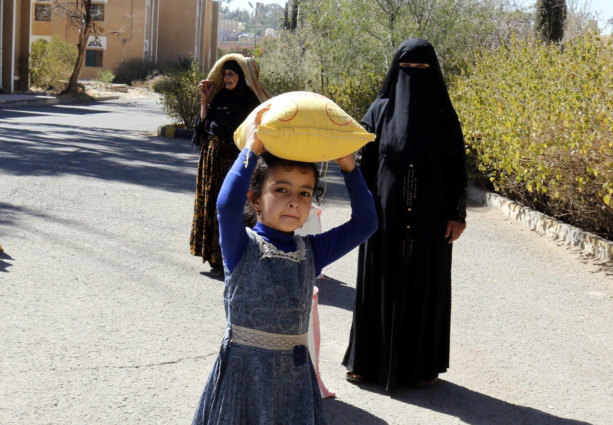 Jemen: dziecko jemenickich Żydów niesie racje żywnościowe otrzymane od organizacji Mona Relief Yemen w Sanie, obszarze pod kontrolą jemenickiego wojska. Społeczność ta, pomimo izraelskich operacji z 1948 roku liczy do dziś na obszarze Sany 67 Żydów z 17 rodzin, fot: Yahya Arhab, PAP/EPA