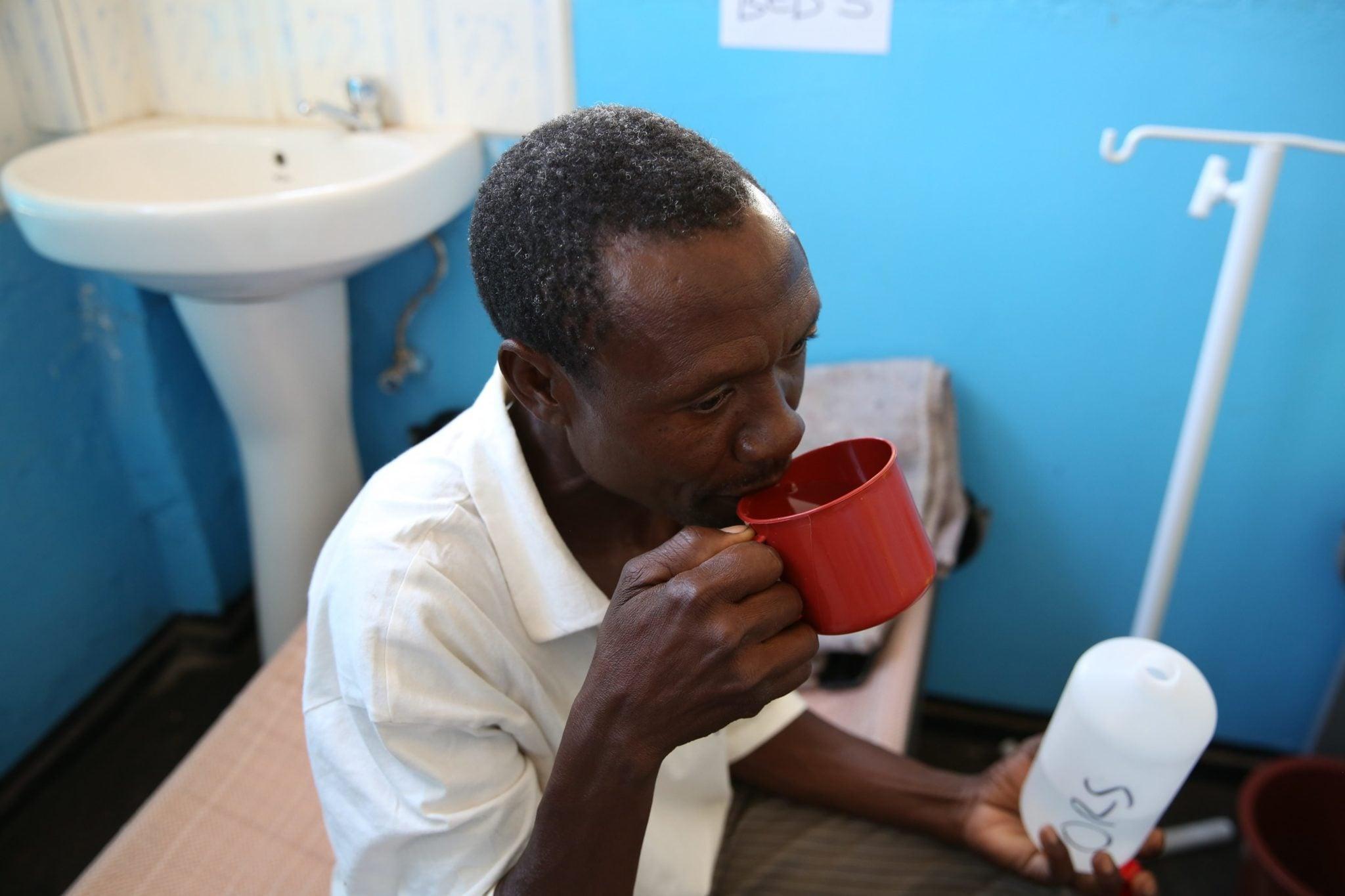 Zimbabwe: pacjent, u którego podejrzewa się cholerę pije roztwór przygtowany dla niego w klinice, fot: