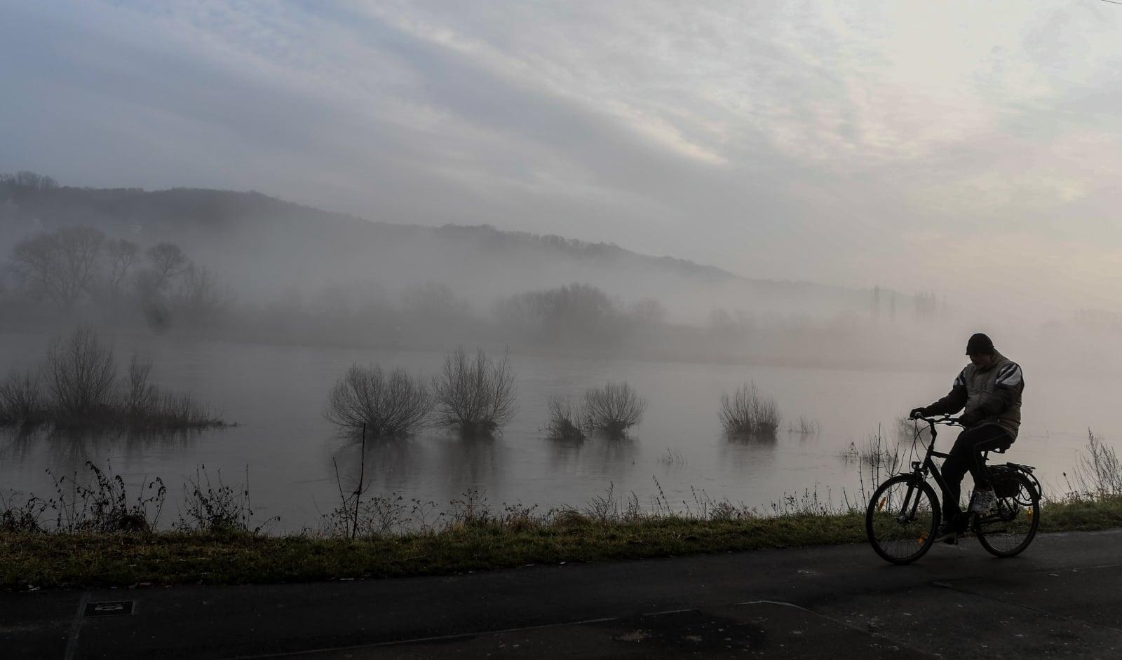 Mężczyzna jadący na rowerze w mglisty poranek koło Drezna, Niemcy, fot.EPA/FILIP SINGER