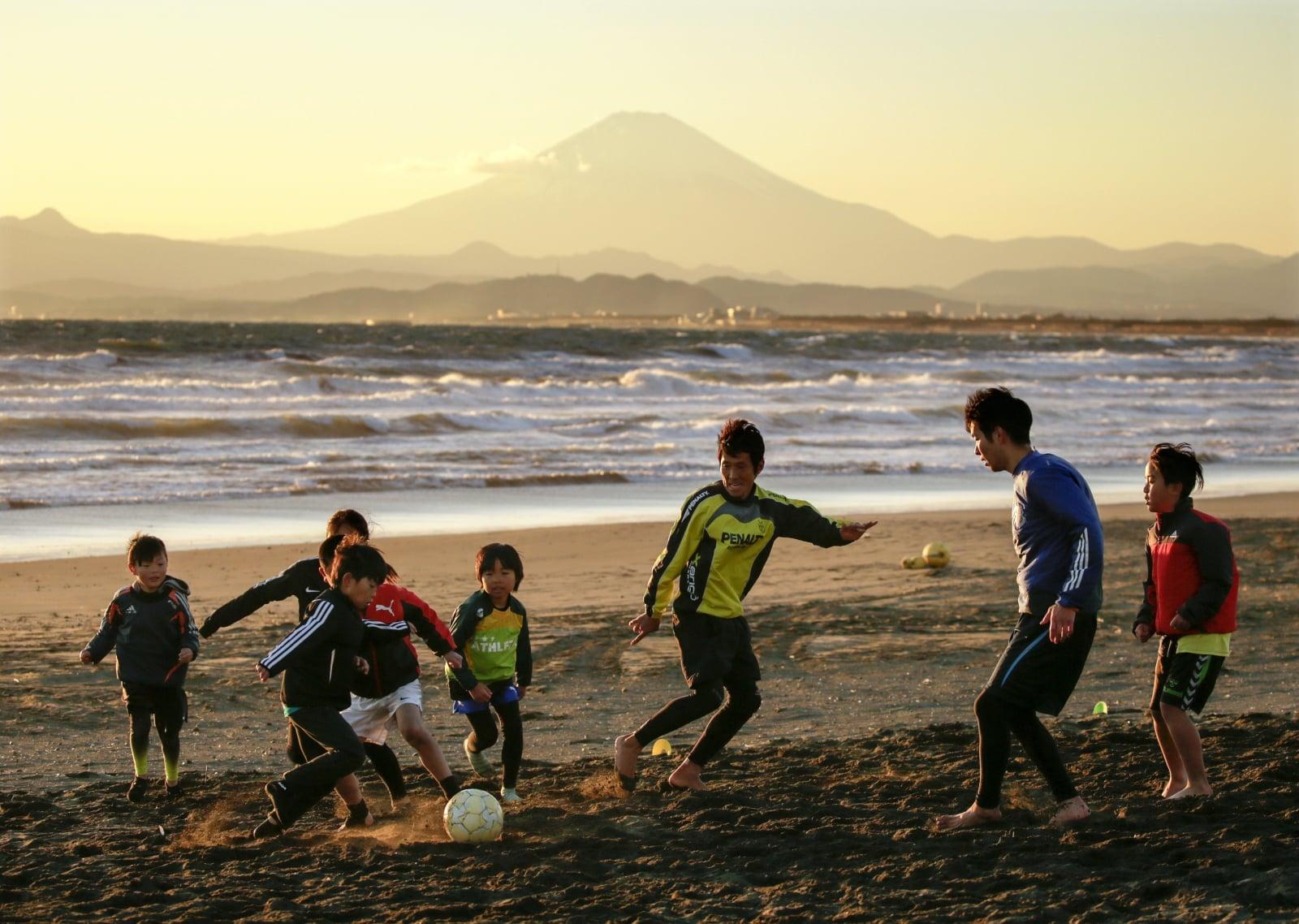 Dzieci grające w piłkę na plaży, Japonia, fot.EPA/KIMIMASA MAYAMA
